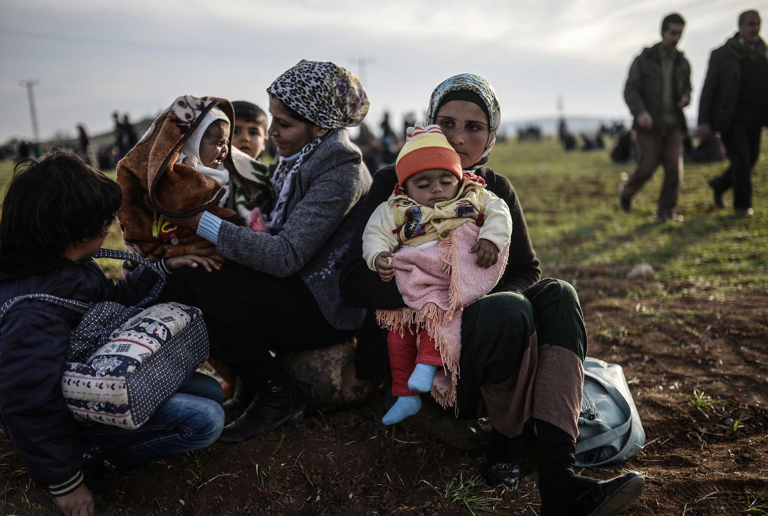 Syrian Kurdish women sit with their children near the Turkish-Syrian border in Suruc, Turkey, on Jan. 27, 2015.