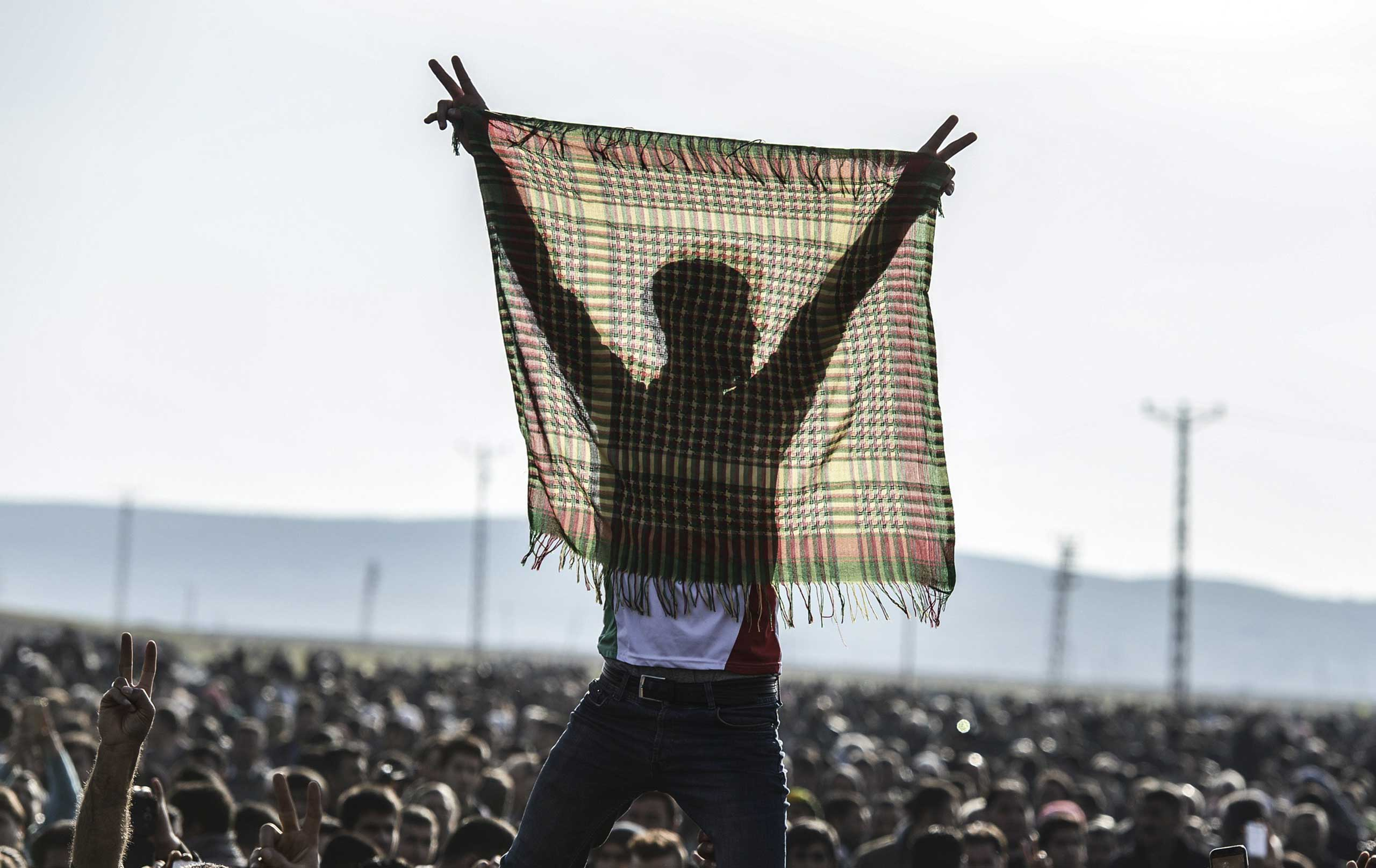 A man holds up a scarf at a celebration rally near the Turkish-Syrian border in Suruc, Turkey, on Jan. 27, 2015.