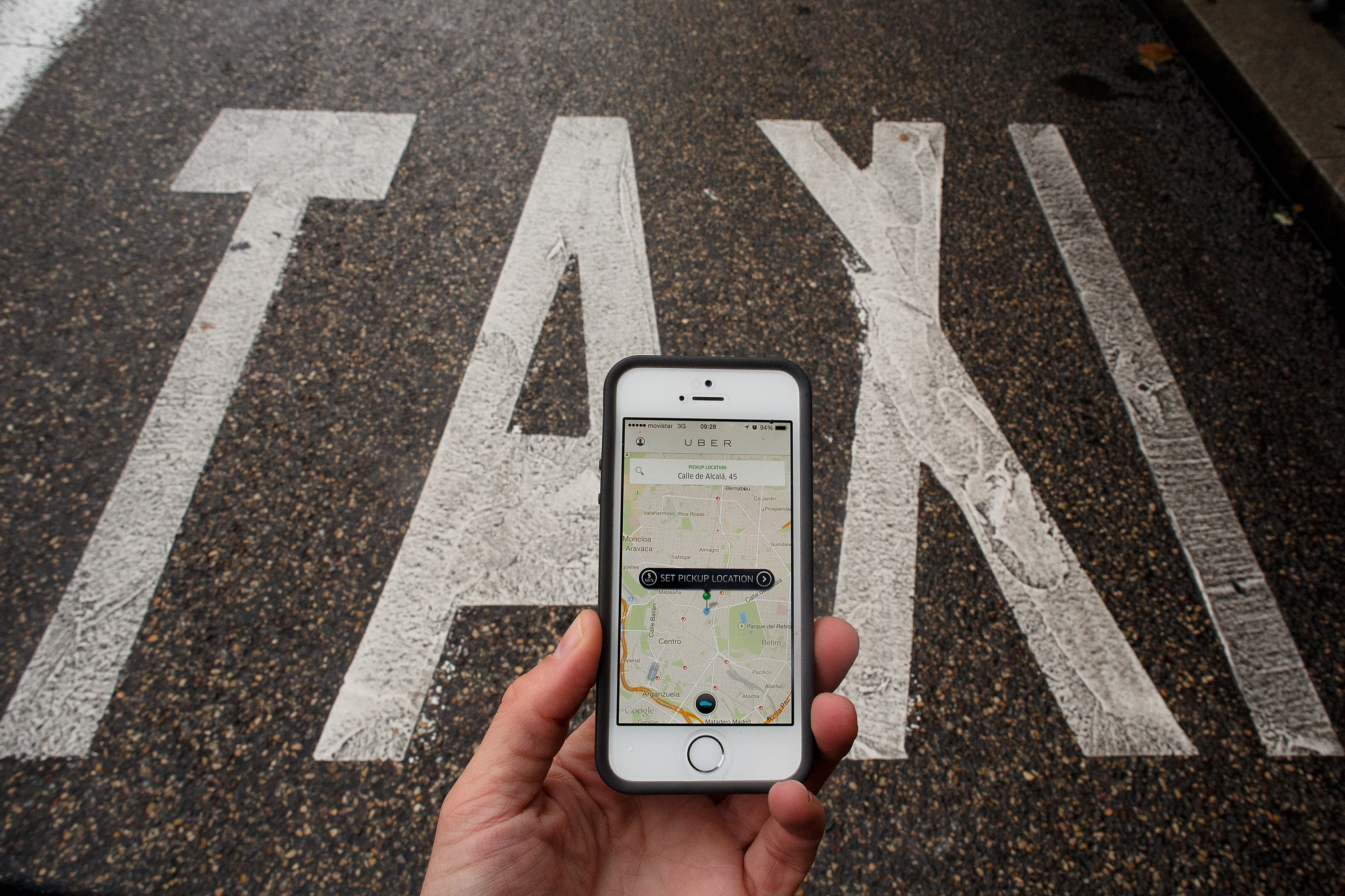 In this photo illustration the smart phone taxi app Uber shows how to select a pick up location next to a taxi lane on Oct. 14, 2014 in Madrid, Spain.