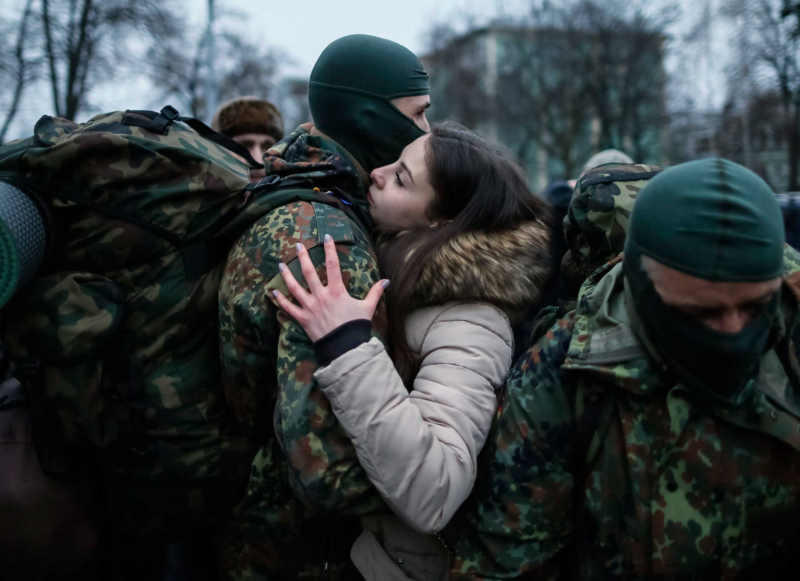 A new volunteer for the Ukrainian Interior Ministry's Azov battalion embraces his girlfriend before he and other volunteers depart to the frontlines in eastern Ukraine, in central Kiev on Jan. 17, 2015.