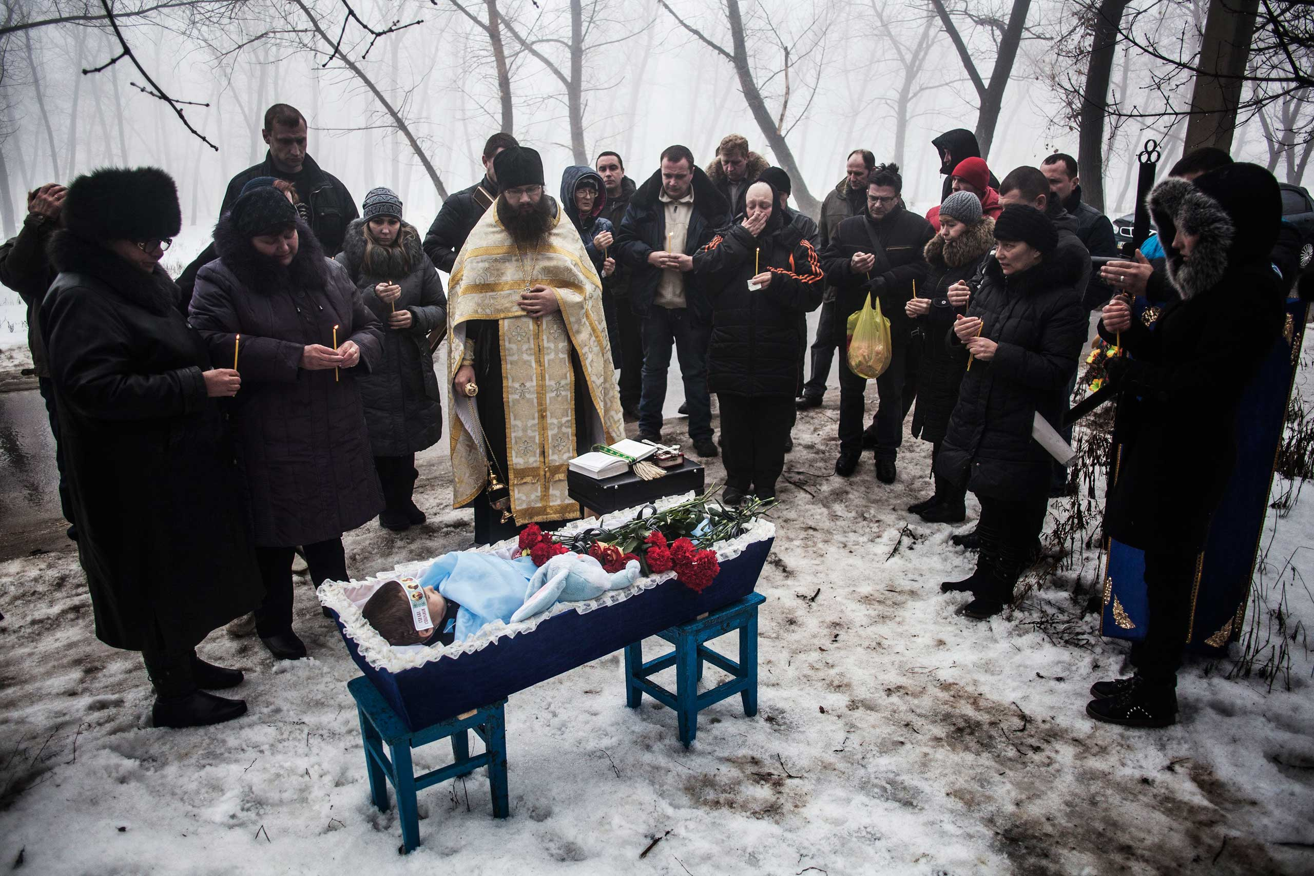 Paris Match L'Instant: In Ukraine, The Frozen Tears of Donetsk Mourners gather around a coffin bearing Artiam, 4, who was killed in a Ukrainian army artillery strike, during his funeral in Kuivisevsky district on the outskirts of Donetsk, eastern Ukraine, Jan. 20, 2015.