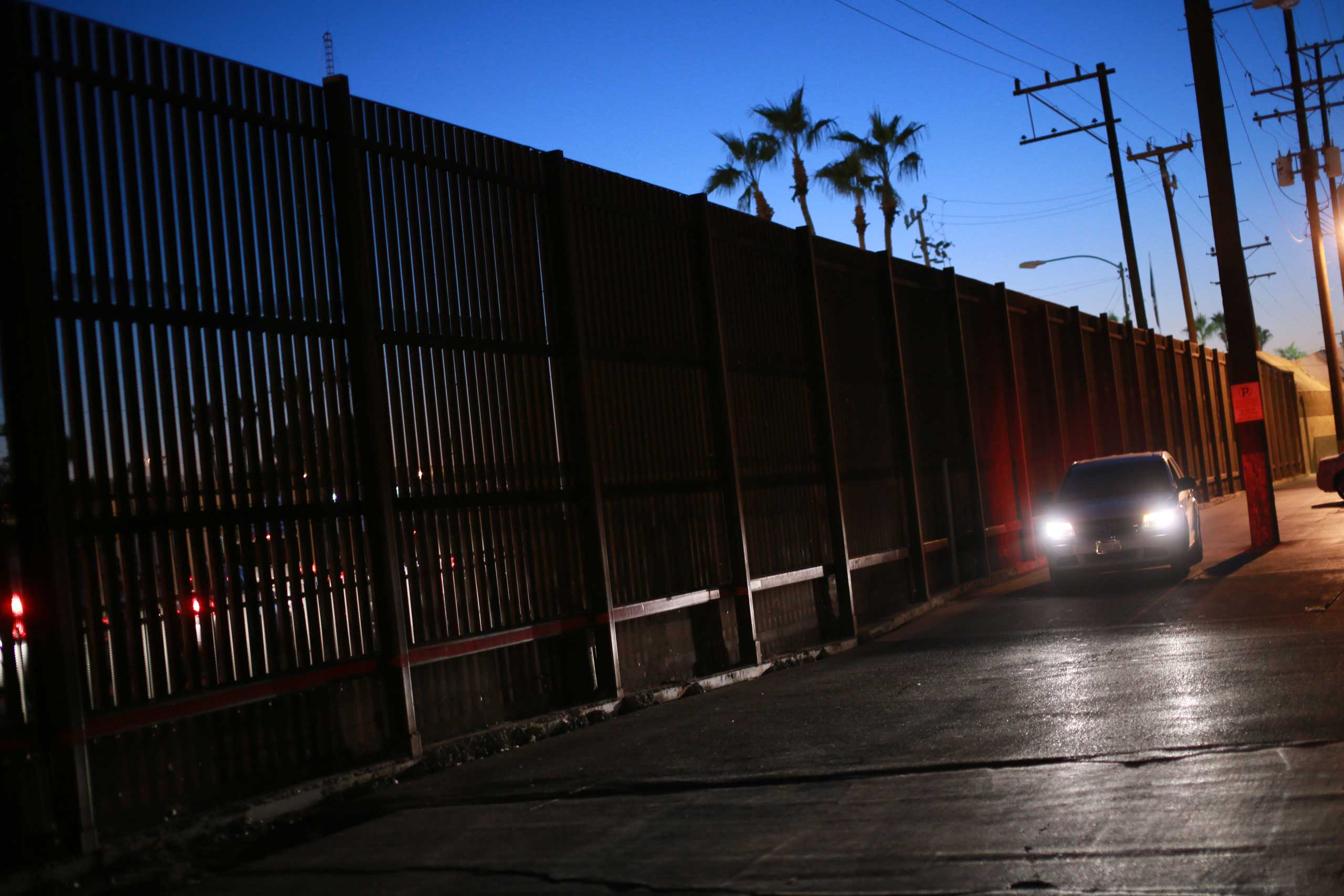 A car drives along the U.S. - Mexico border wall in Calexico, Calif. on Nov. 19, 2014.