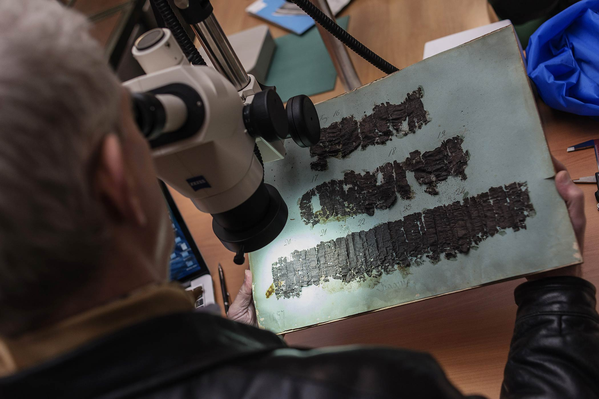 David Blank, professor of Classics from the University of California, looks through a microscope at an ancient papyrus at the Naples' National Library, Italy, Jan. 20, 2015.