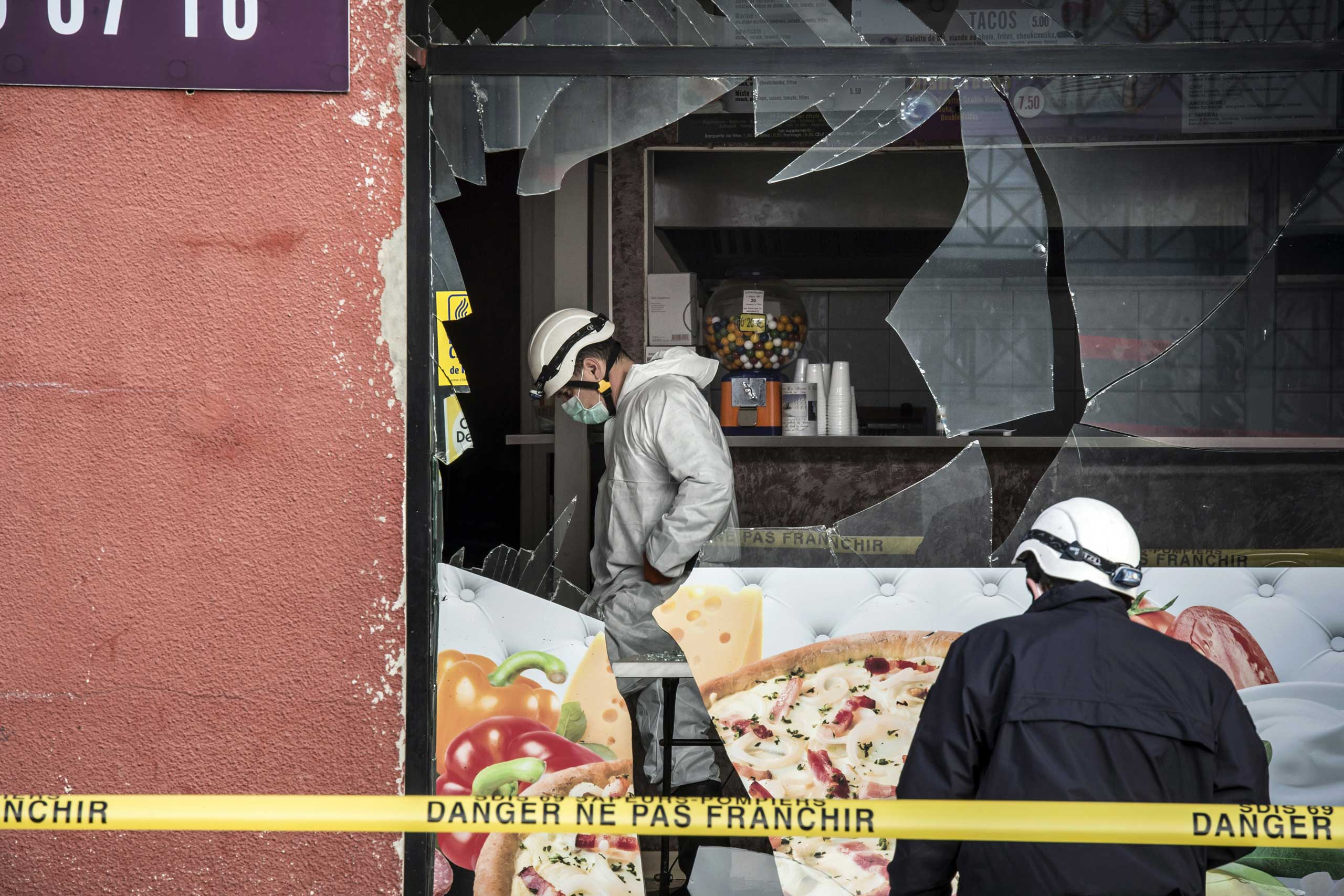 French police forensic scour the scene of an explosion at a kebab shop damaged following an explosion near a mosque, on Jan. 8, 2015, in Villefranche-sur-Saone, eastern France.