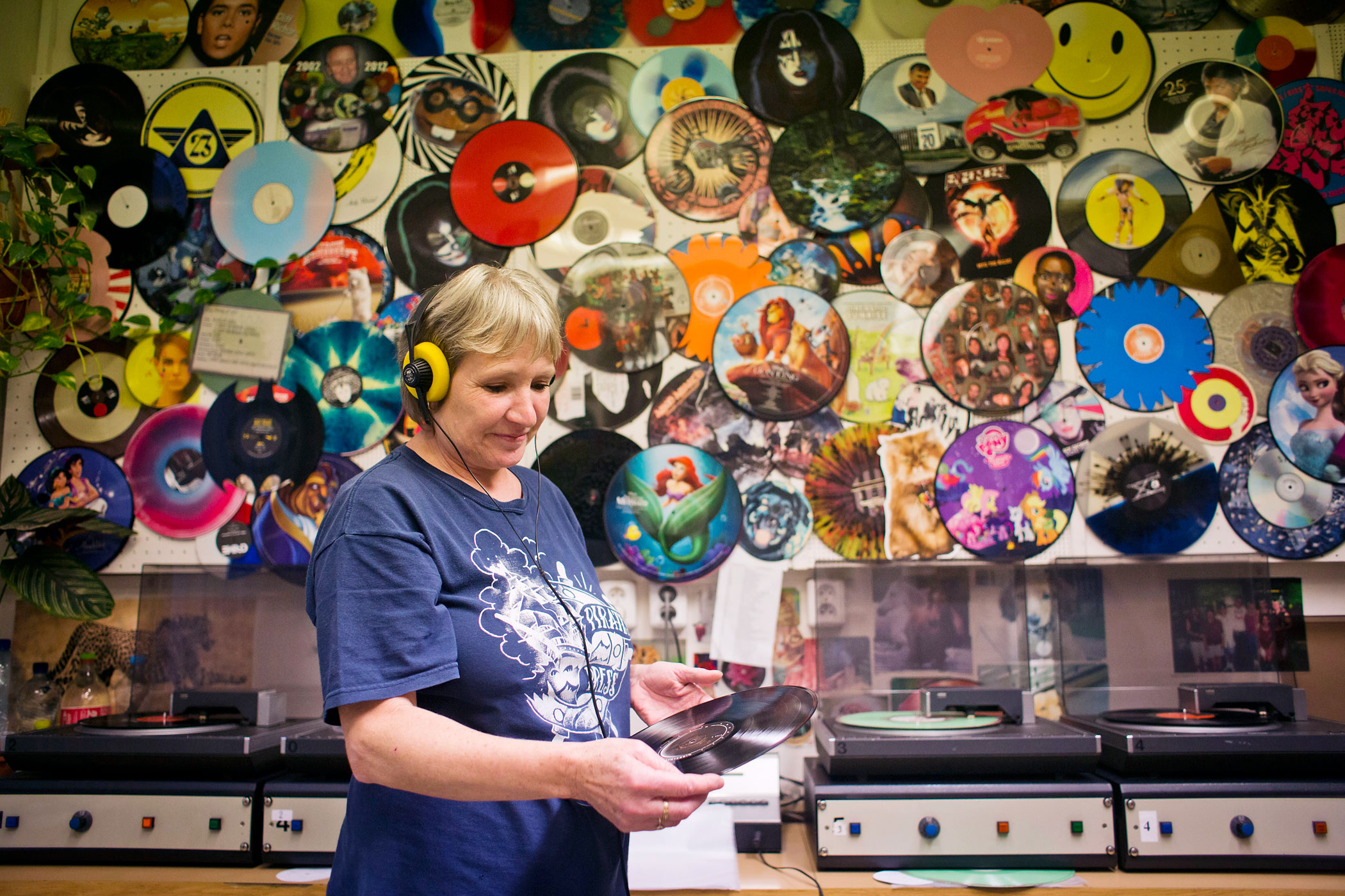 A worker listens through headphones and checks the sound quality of 12  inch vinyl records before they are dispatched, after being manufactured by GZ Media a.s. at their plant in Lodenice, Czech Republic, on Nov. 25, 2014.