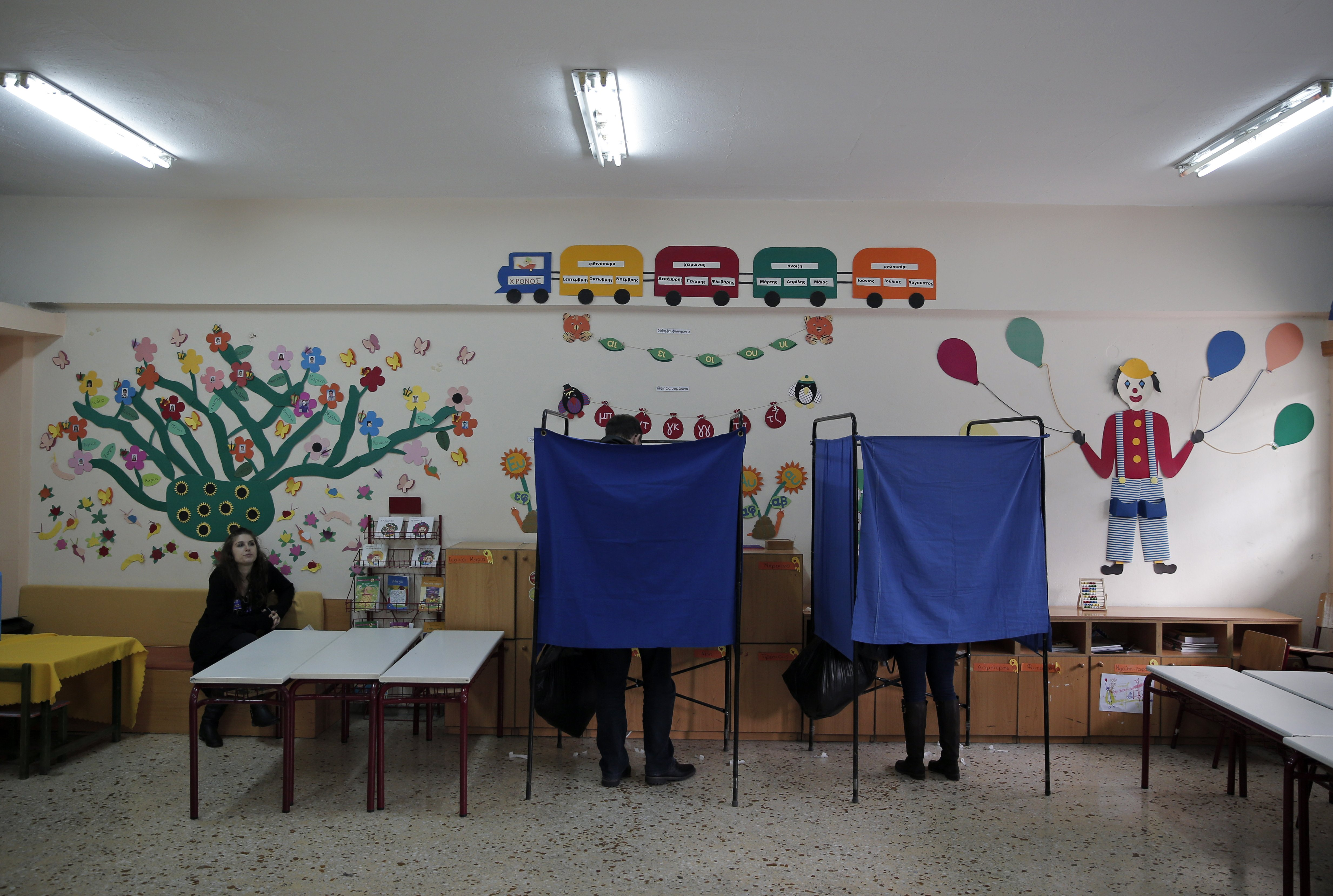 People cast their ballots in booths at a polling station in an Athens school on Jan. 25, 2015.