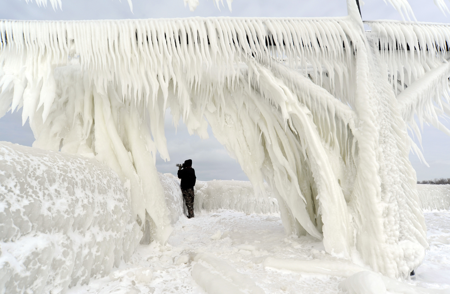 Ice coats the railings leading to the North Pier Lighthouses as a photographers takes pictures on Jan. 10, 2015, in St. Joseph, Mich.