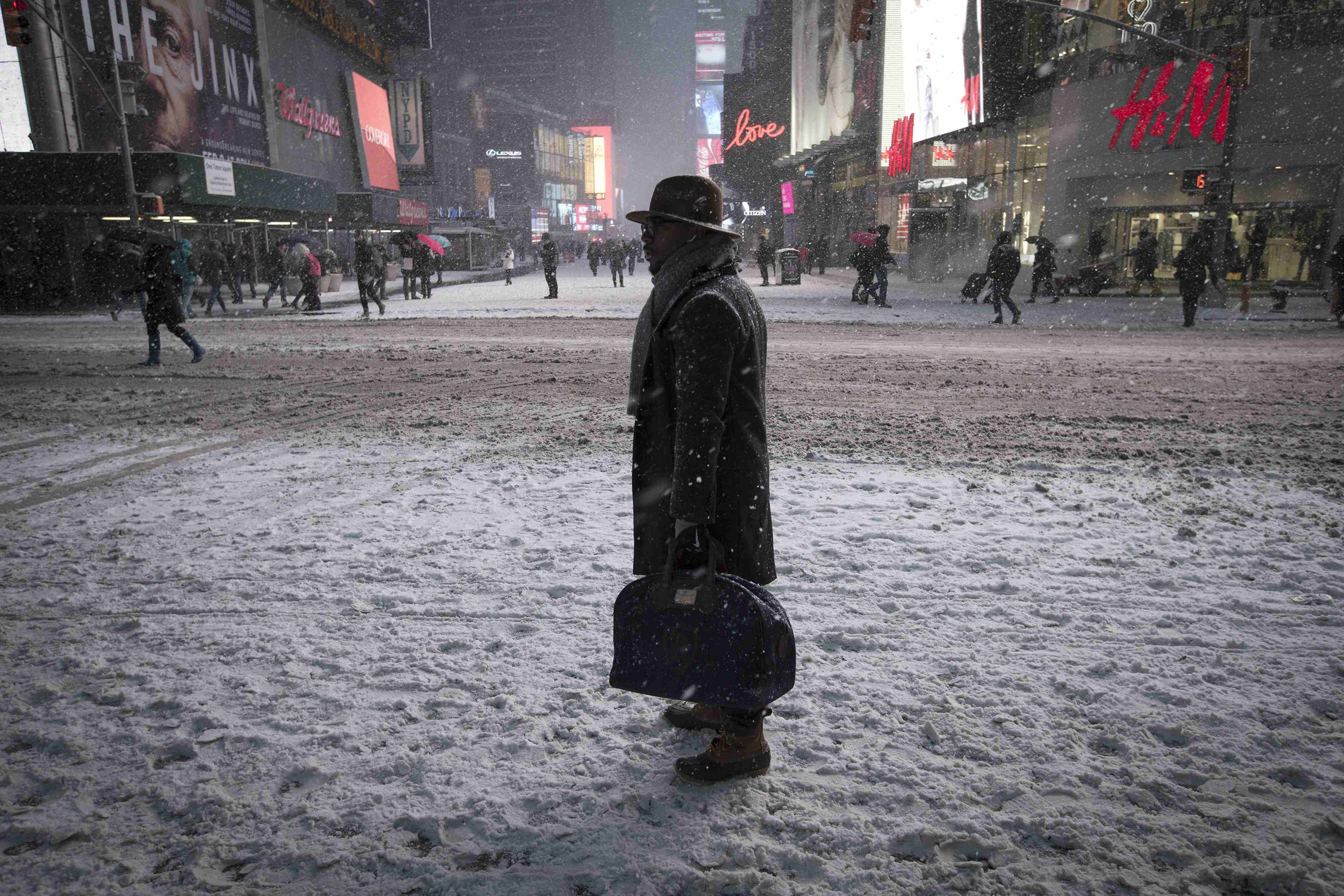 A man stands in falling snow on West 42nd street in Times Square in New York City on Jan. 26, 2015.