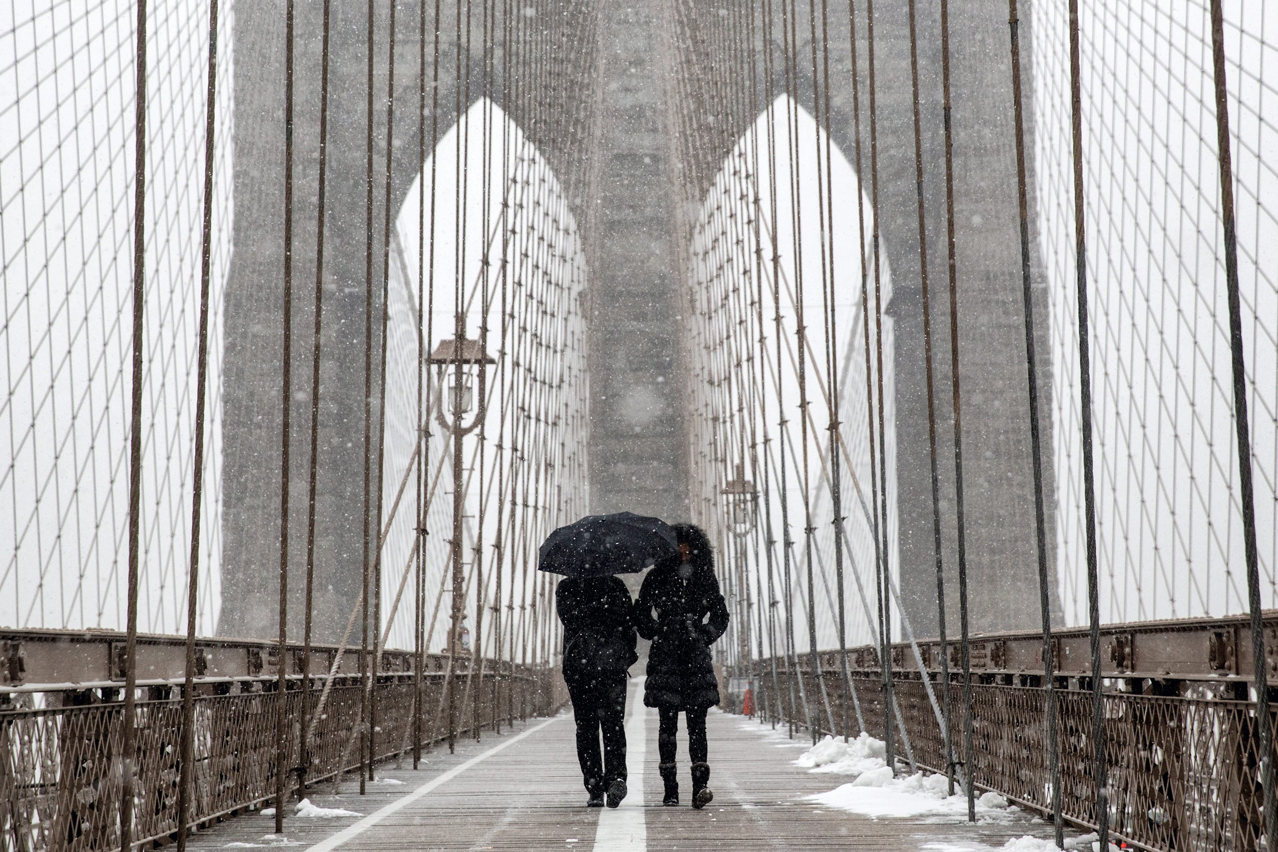 People walk over the Brooklyn Bridge during a large winter storm in New York City on Jan. 26, 2015.