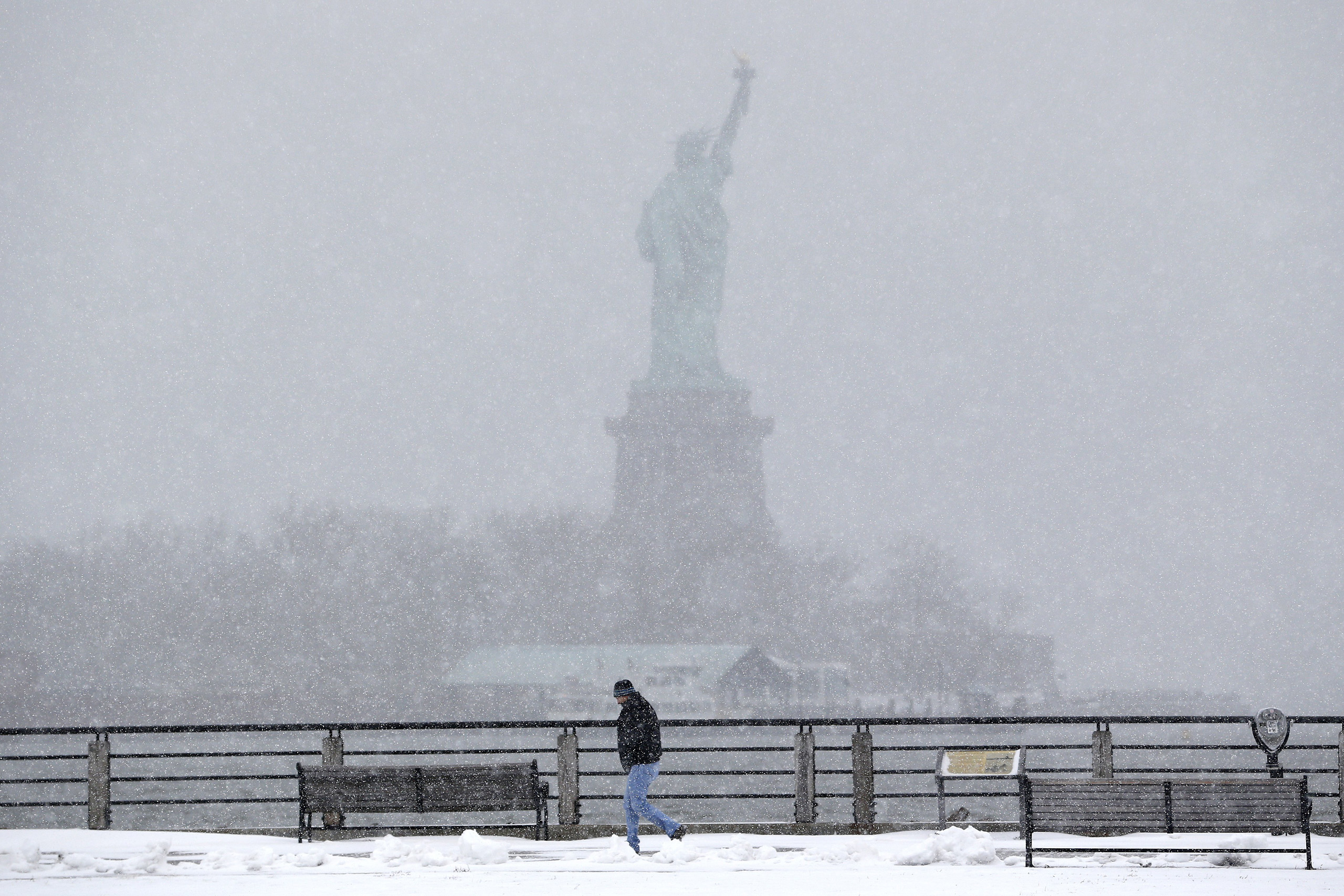 A man strolls on a walking path at Liberty State Park, with the Statue of Liberty in the distance, in Jersey City, N.J. on Jan. 26, 2015.