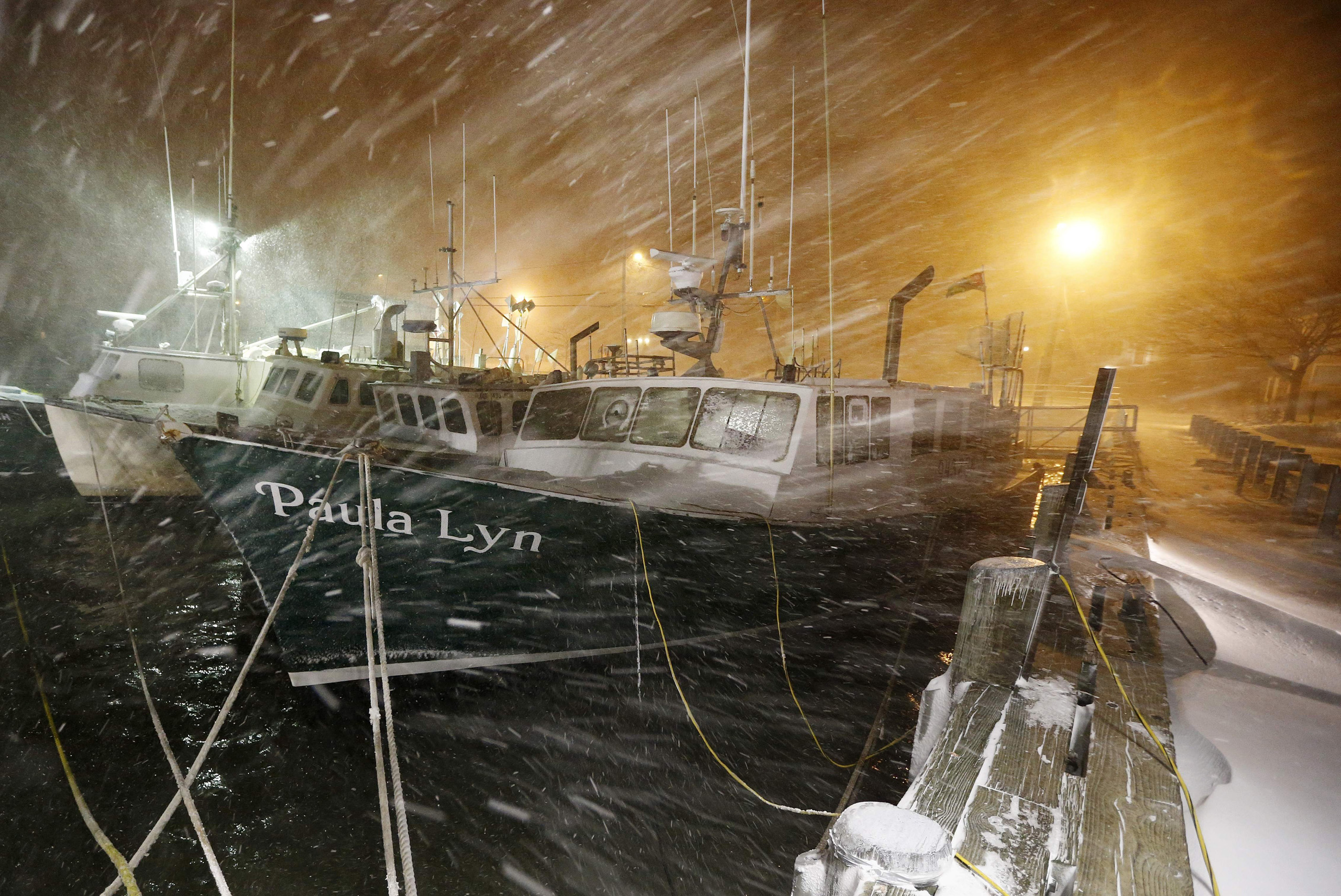 Fishing boats ride out the storm at dock in Scituate, Mass., on Jan. 27, 2015.