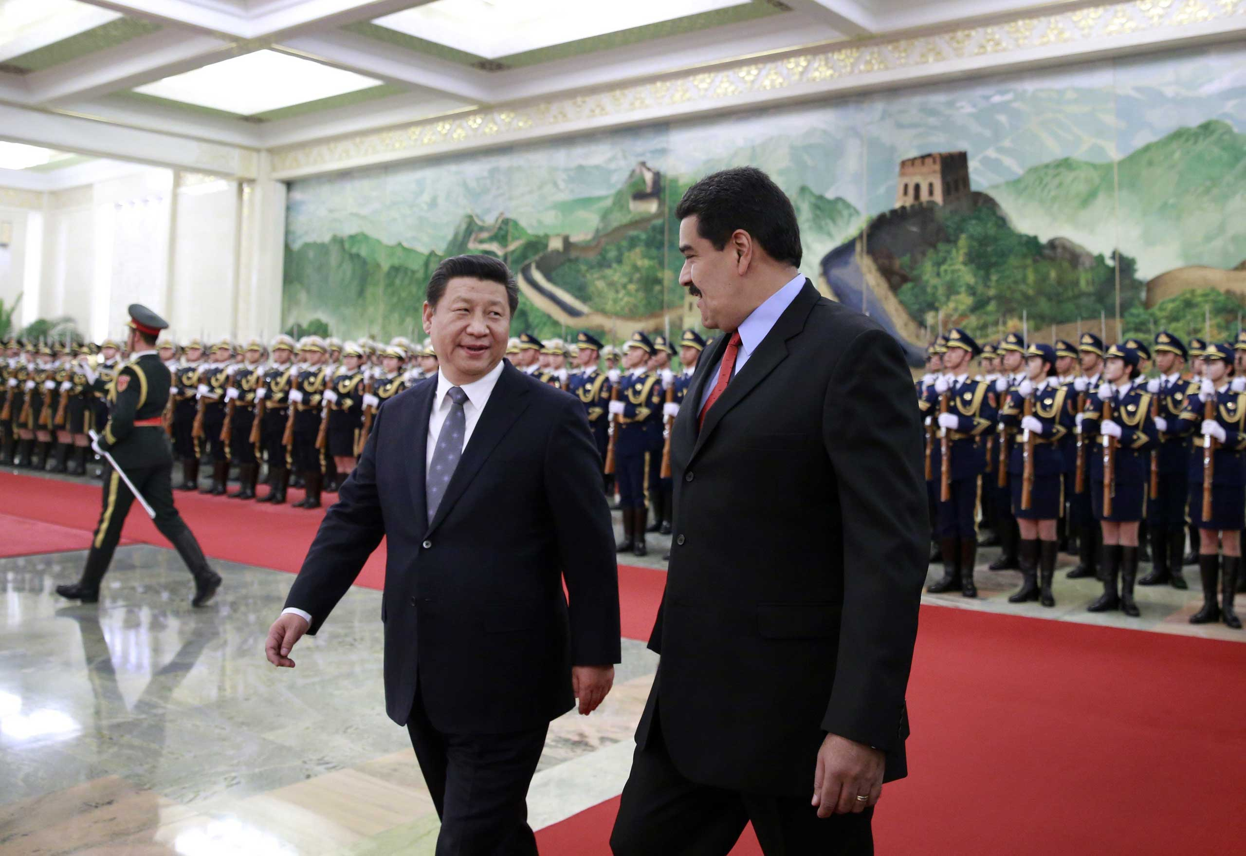 Venezuela's President Nicolas Maduro and Chinese President Xi Jinping chat after reviewing an honor guard during a welcome ceremony at the Great Hall of the People in Beijing on Jan. 7, 2015.