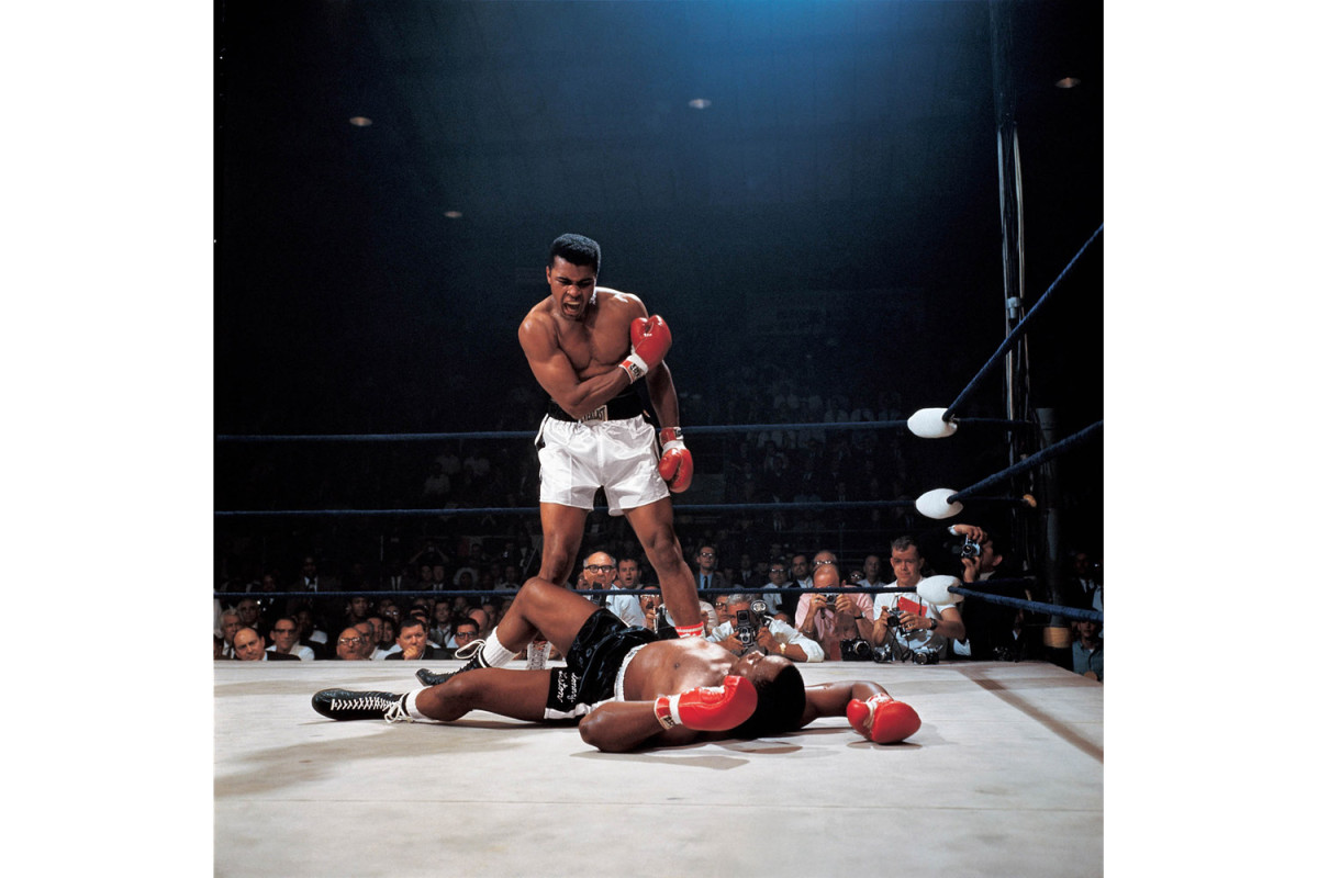 Ali after knocking down Sonny Liston in Lewiston, Maine, 1965                                                              Don Delliquanti:  Attorneys have a rule to never ask a question to which they already do not know the answer. Unfortunately for me, I did not learn this rule until I had asked such a question. In October of 1971, I was riding in a rented station wagon back to New York City with some Sports Illustrated photographers who had finished photographing the final World Series game. One of the photographers was the late Herb Scharfman, a veteran who was equally skillful photographing both baseball and boxing. Somewhere along the New Jersey Turnpike, I began talking boxing with Herb and happened to ask if he was the SI photographer who shot the famous photo of Muhammad Ali standing over Sonny Liston. Herbie answered with an icy 'No,' and our conversation ended abruptly. A few days after we returned to New York City, I noticed the Neil Leifer photo hanging on a wall at SI, and there was Herbie Scharfman in the photo on the opposite side of the ring between Ali's legs, exactly 180 degrees away from one of the greatest photos ever taken ... and then I knew!                                Don Delliquanti is the former deputy picture editor and a 25-year veteran at Sports Illustrated.