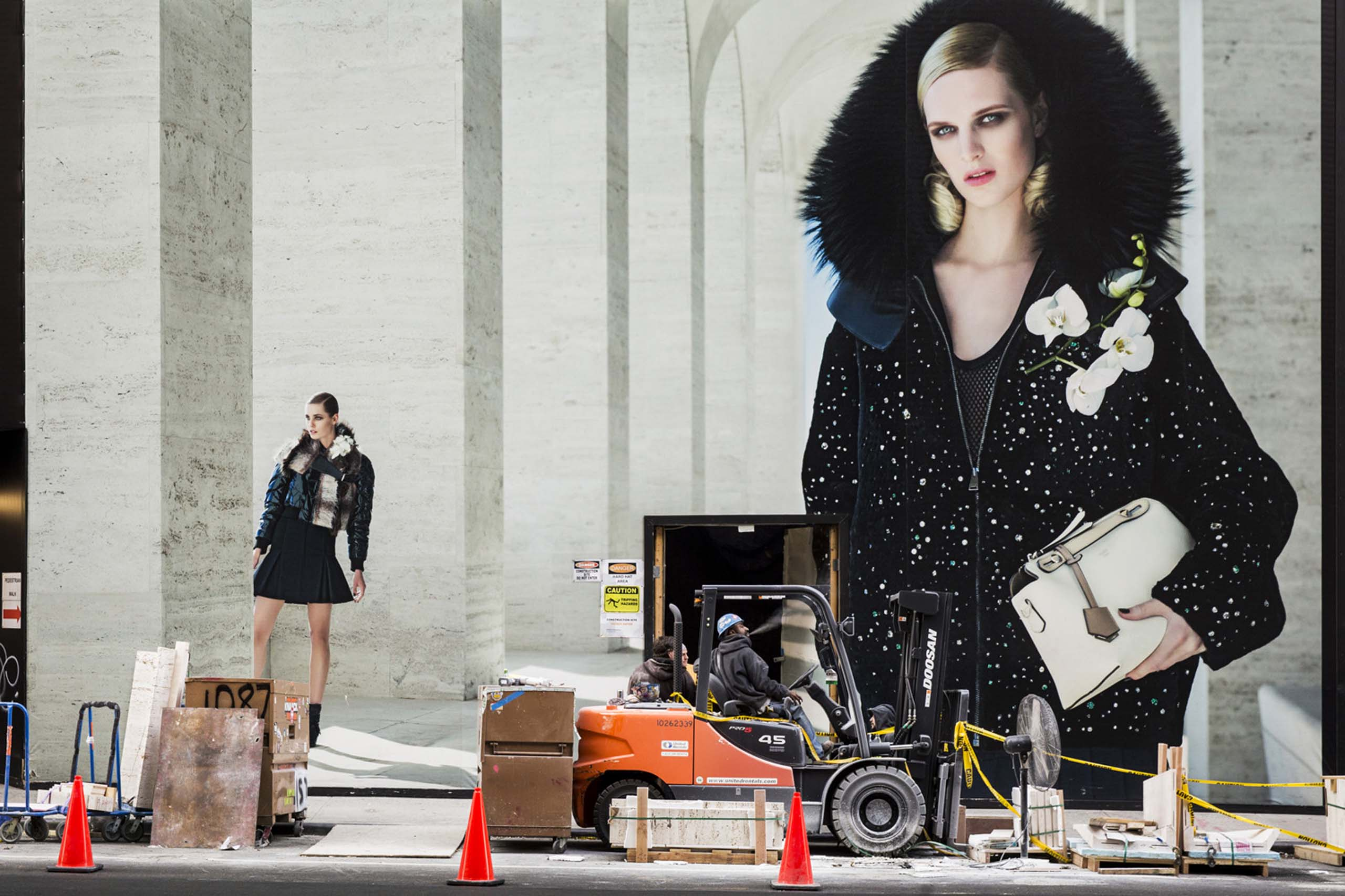 A construction worker enjoys a cigarette break next to a Fendi billboard on Madison Avenue, New York, Nov. 09, 2014.