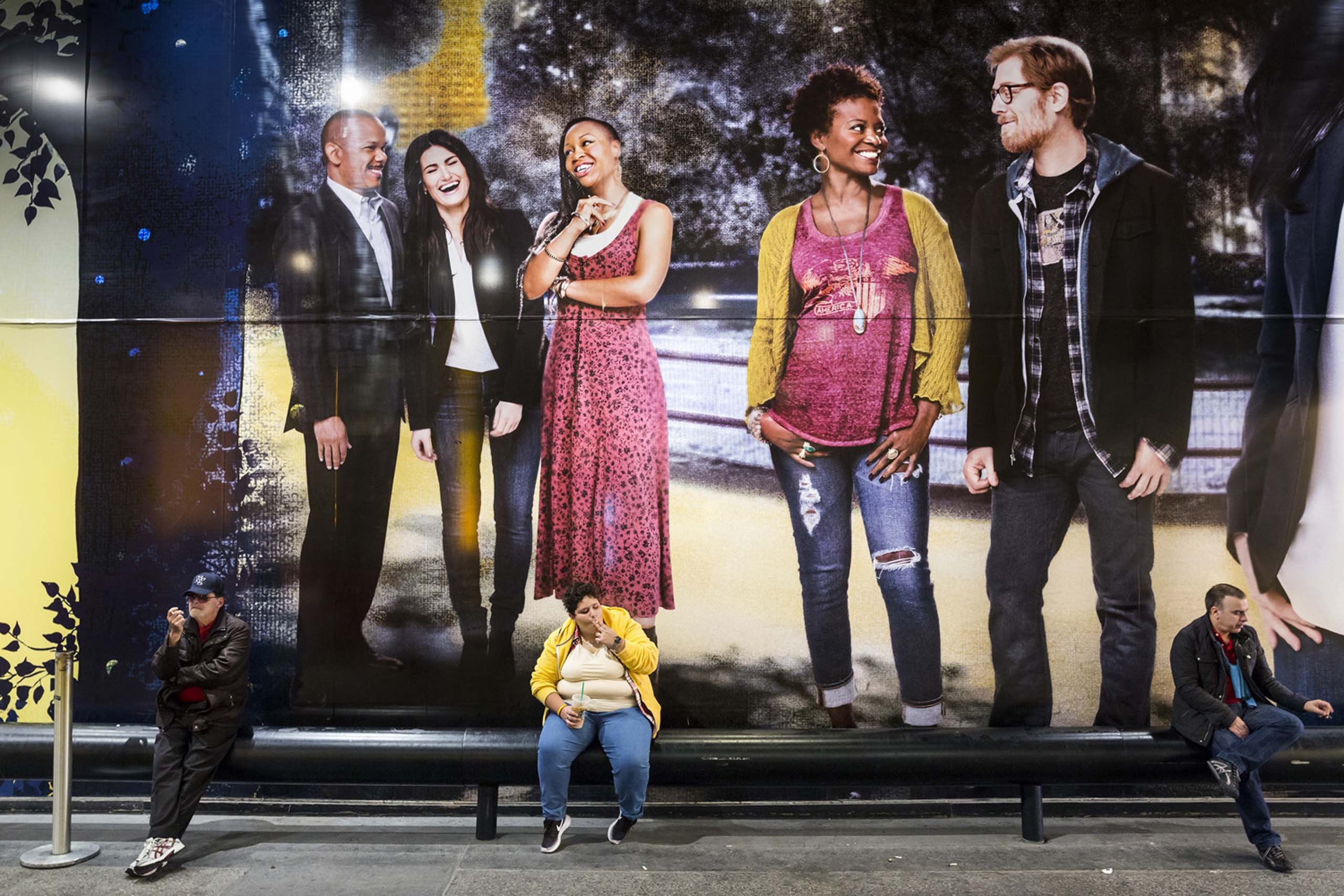 Apr 22, 2014 - New York, New York, United States: Three people smoking under a billboard promoting the Broadway show Once around Times Square. (Natan Dvir / Polaris Images)