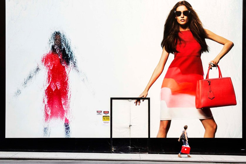 A woman holding a red shopping bag passes by a Fendi billboard on Madison Avenue, New York, June 21, 2014.