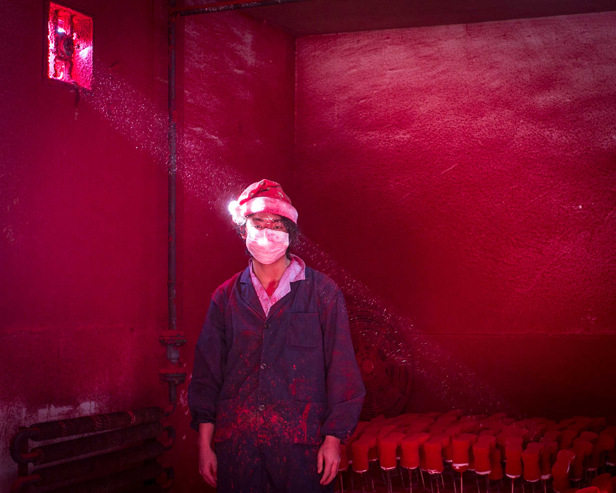 <b>Second Prize Contemporary Issues Category, Singles</b>Wei, a 19-year-old Chinese worker, wearing a face mask and a Santa hat, stands next to Christmas decorations being dried in a factory as red powder used for coloring hovers in the air.