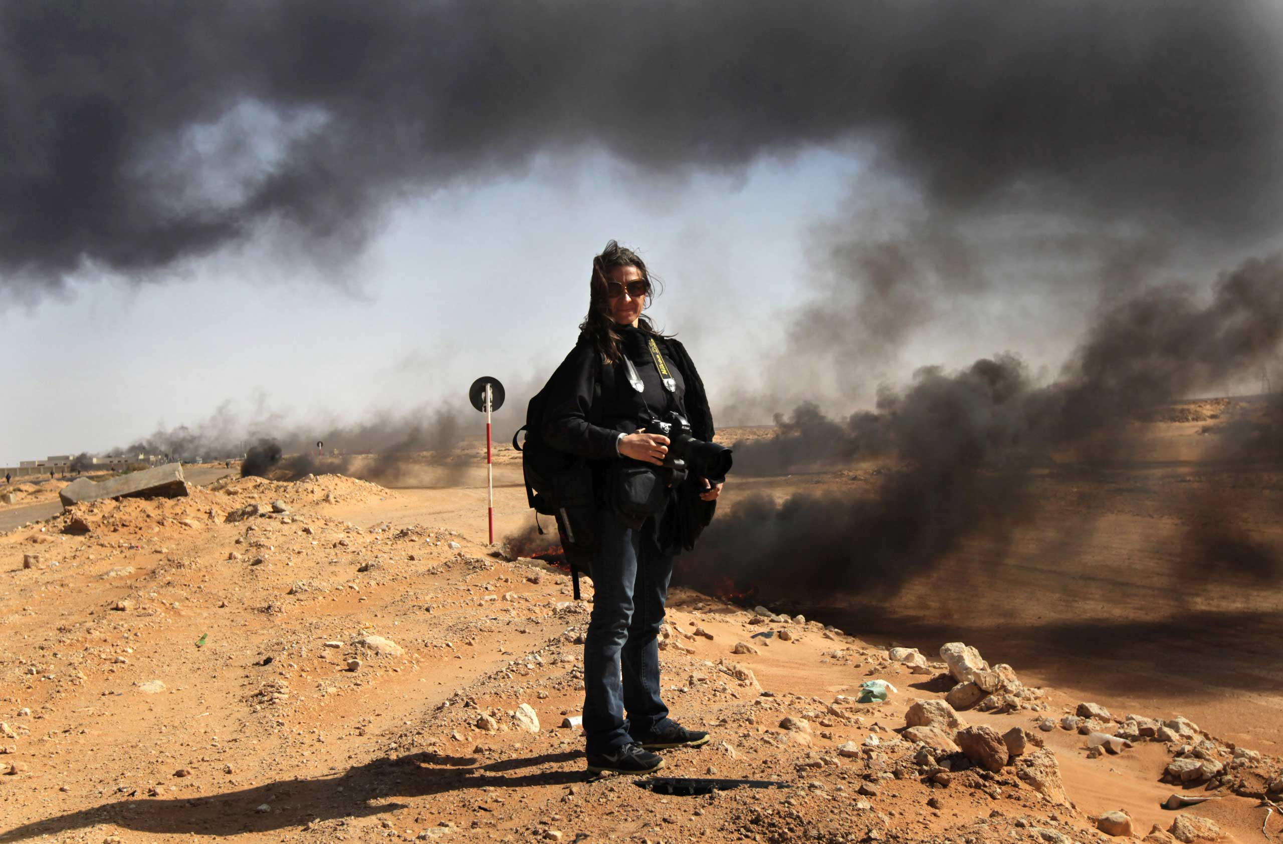 Photographer Lynsey Addario stands near the frontline during a pause in the fighting March 11, 2011 in Ras Lanuf, Libya.