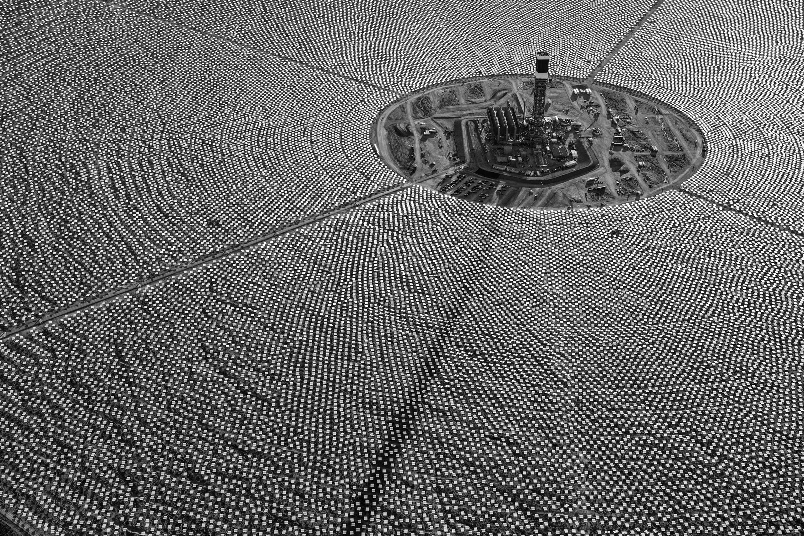 Mirrored heliostats that reflect and concentrate desert sunshine surround a tower at the Ivanpah solar power station in the Mojave Desert, California.