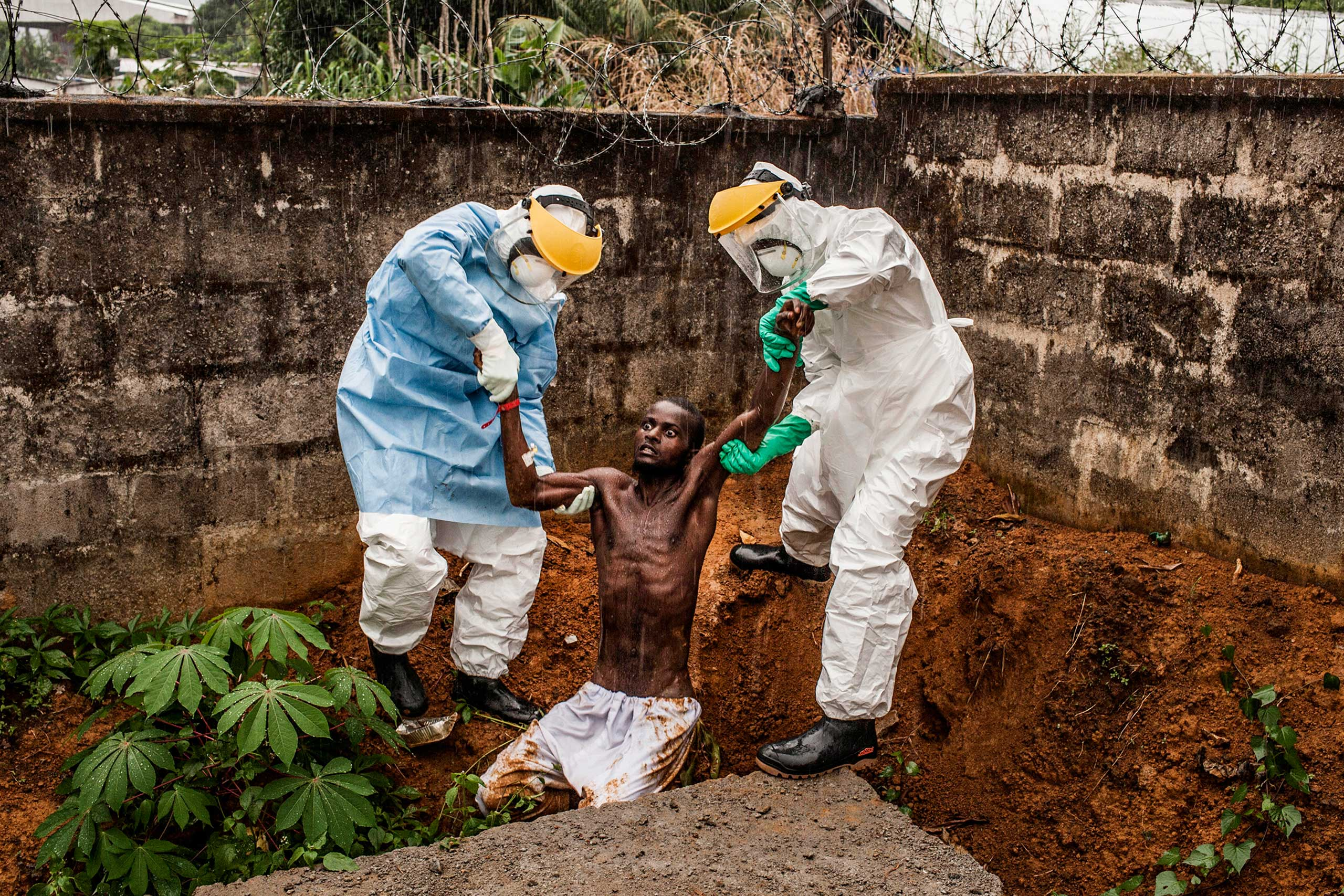 <b>First Prize General News Category, Stories</b>                                   Medical staff at the Hastings Ebola Treatment Center work escort a man in the throes Ebola-induced delirium back into the isolation ward from which he escaped in Hastings, Sierra Leone on Sunday, Nov. 23, 2014.