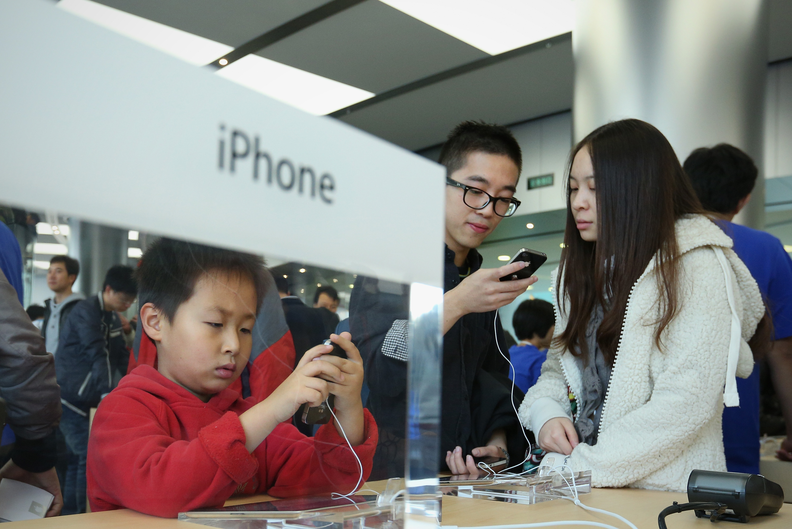 Chinese customers look at iPhone 4S in the newly opened Apple Store in Wangfujing shopping district on October 20, 2012 in Beijing.