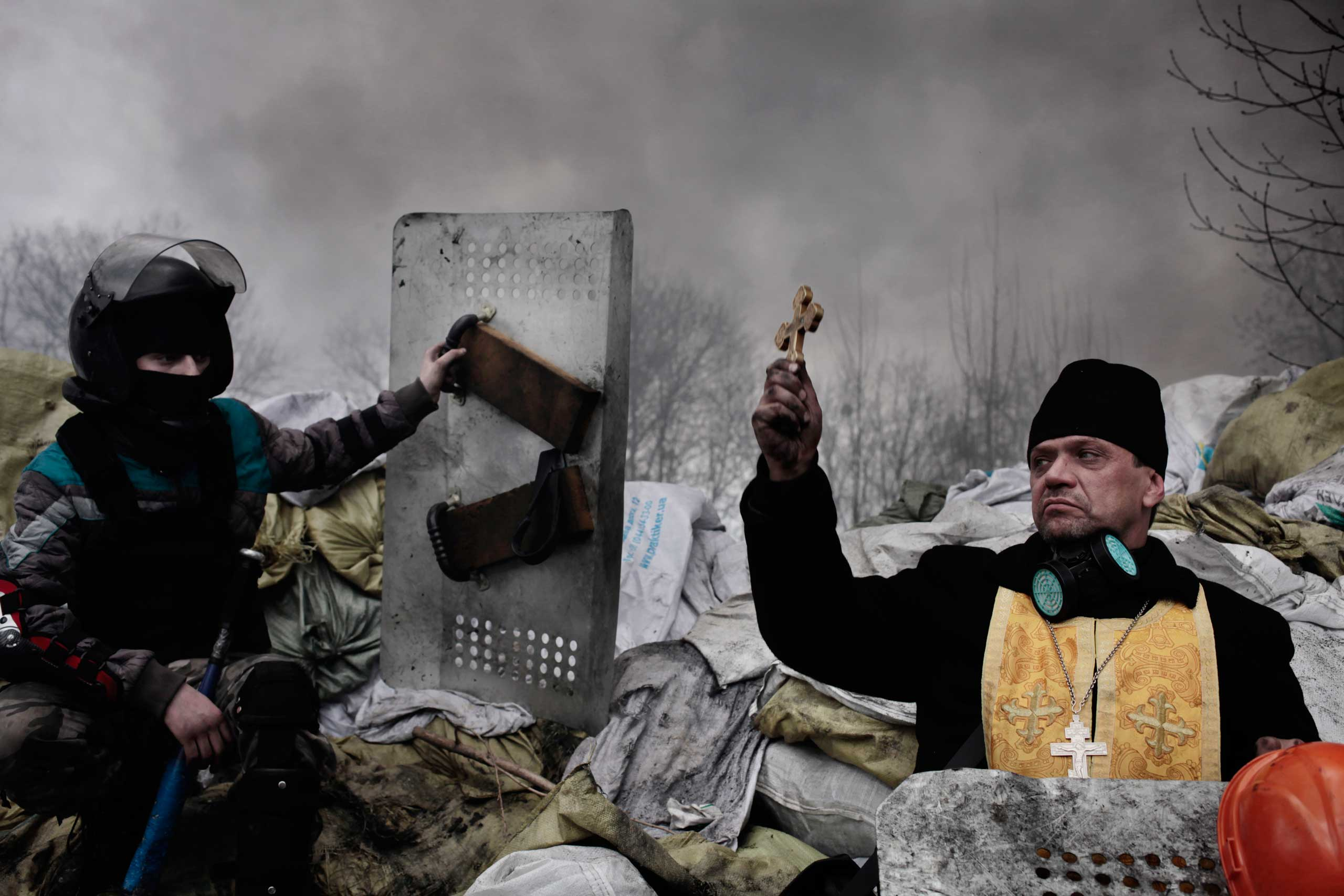 <b>Second Prize Spot News Category, Stories</b>                                   An Orthodox priest bless the protesters on a barricade in Kiev, Ukraine on Feb. 20, 2014.