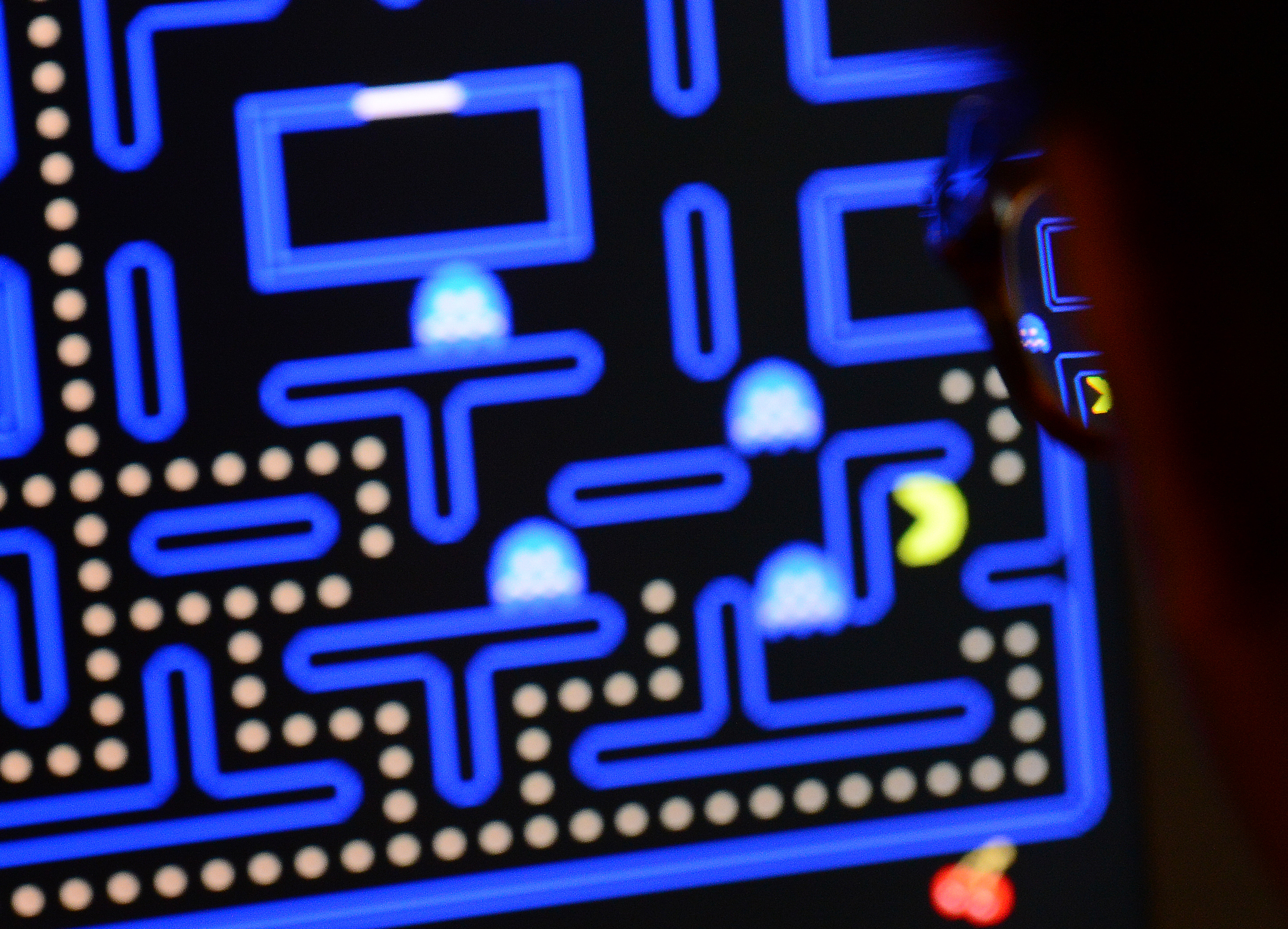 An employee plays the video game Pac-Man (1980) during an exhibition preview featuring 14 video games acquired by The Museum of Modern Art (MoMA)  in New York, March 1, 2013.