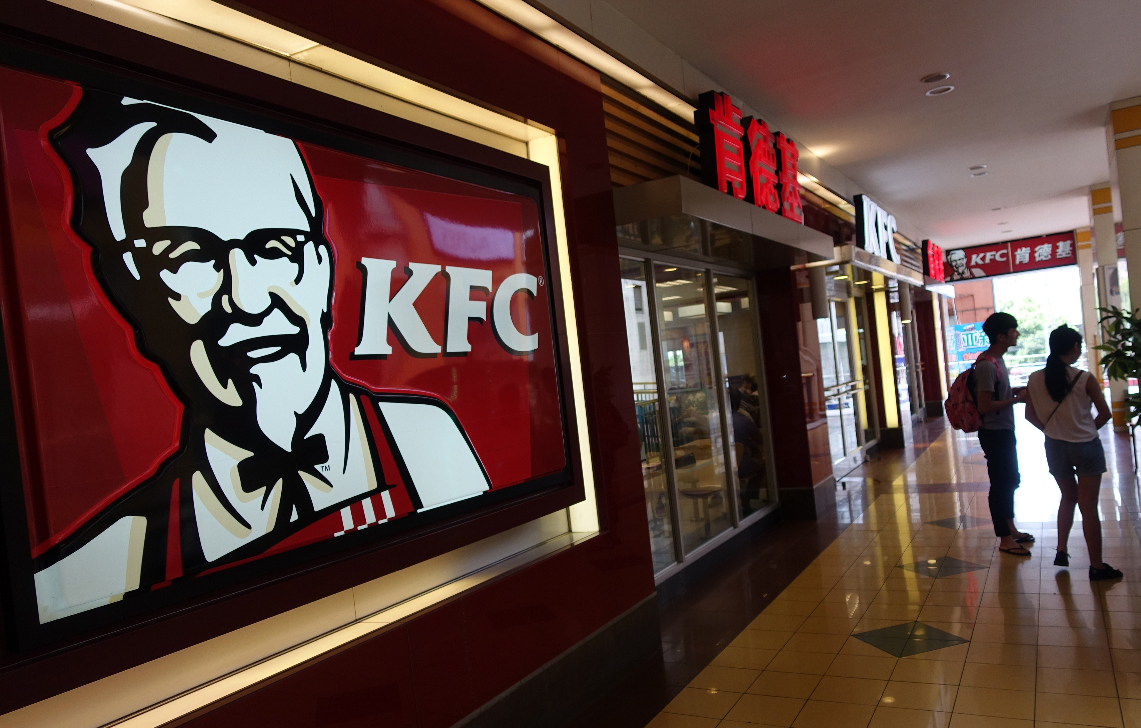 Two people walk past a KFC fast food restaurant in Shanghai on July 23, 2014.
