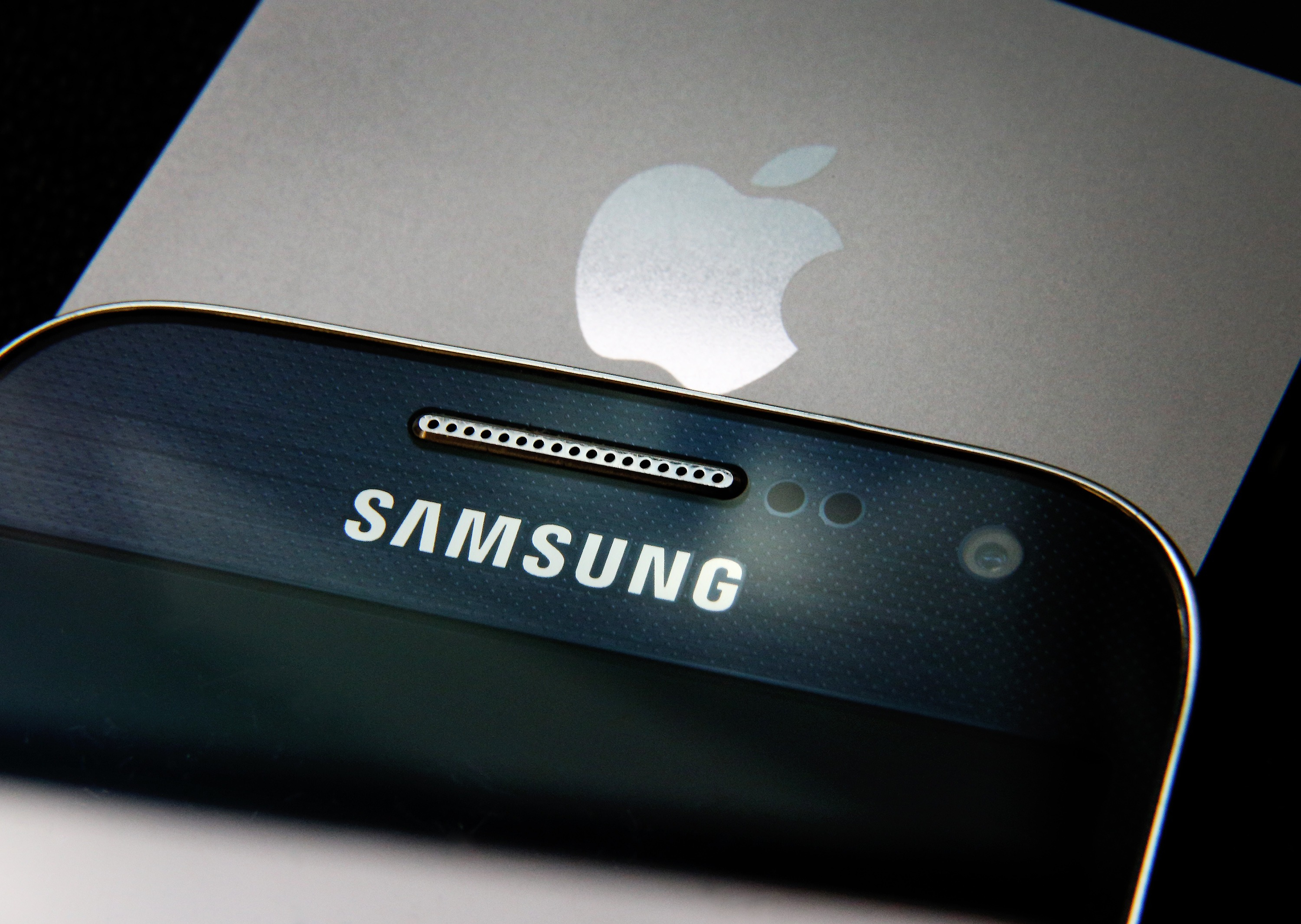 A Samsung and Apple smartphone are displayed on August 6, 2014 in London, England.