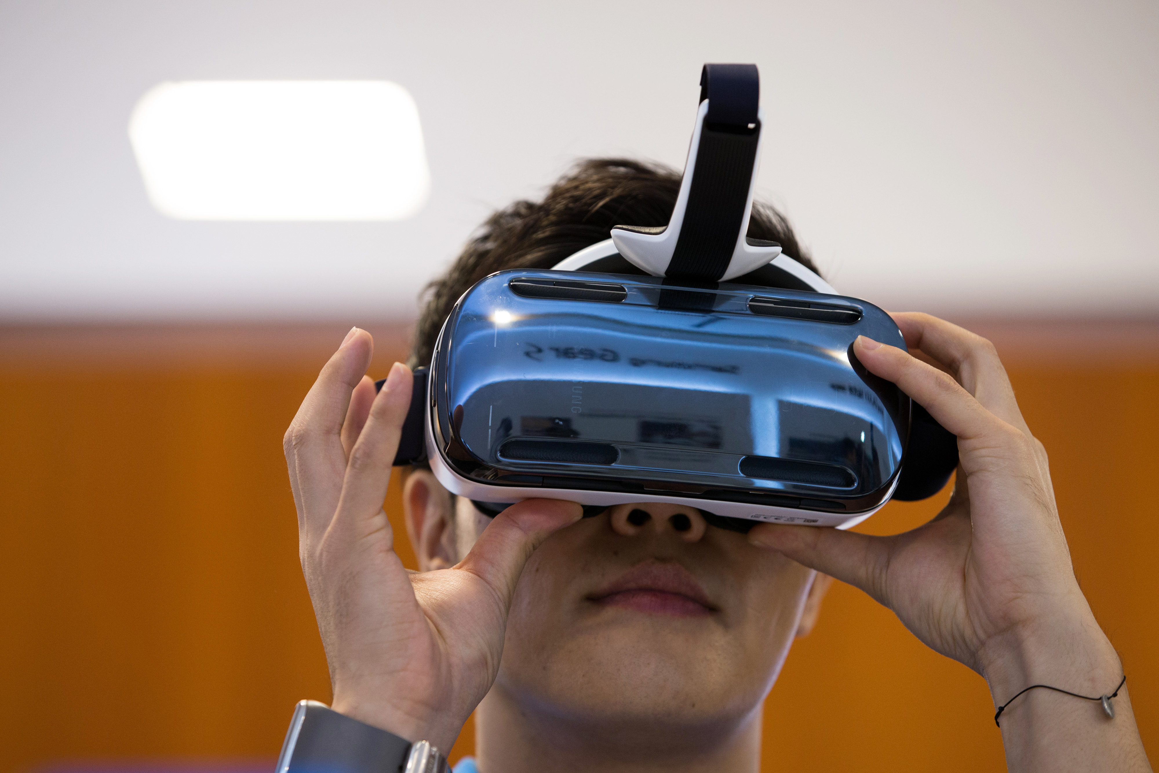 A visitor tries out a Samsung Electronics Co. Galaxy Gear Virtual-Reality (VR) headset, jointly developed by Samsung and Oculus VR Inc., at Samsung's flagship store in Seoul, South Korea, Sept. 24, 2014.