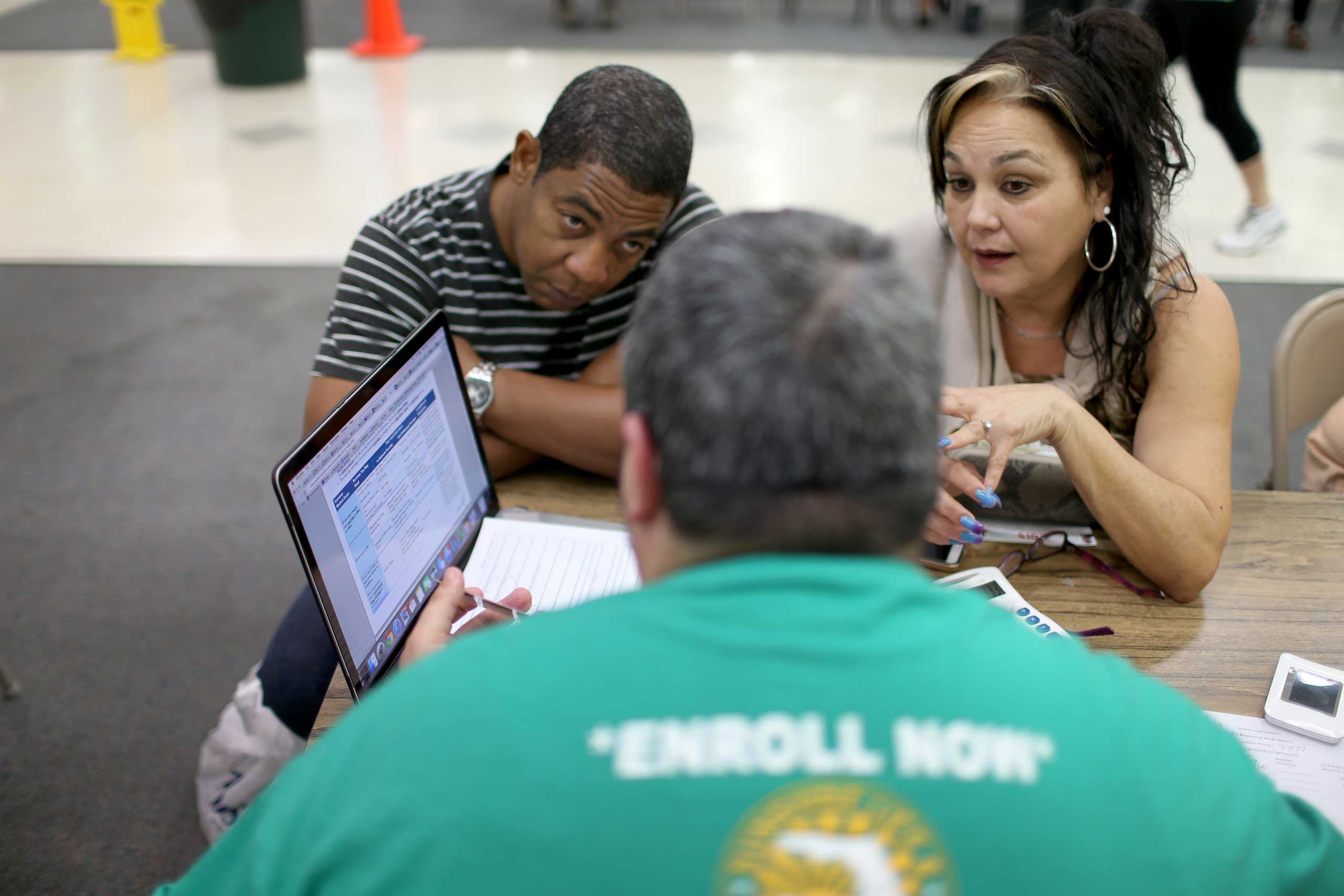 Jose Ramirez, left, and Mariana Silva speak with Yosmay Valdivia, an agent from Sunshine Life and Health Advisors, as they discuss plans available from the Affordable Care Act in the Mall of the Americas on Dec. 15, 2014 in Miami.