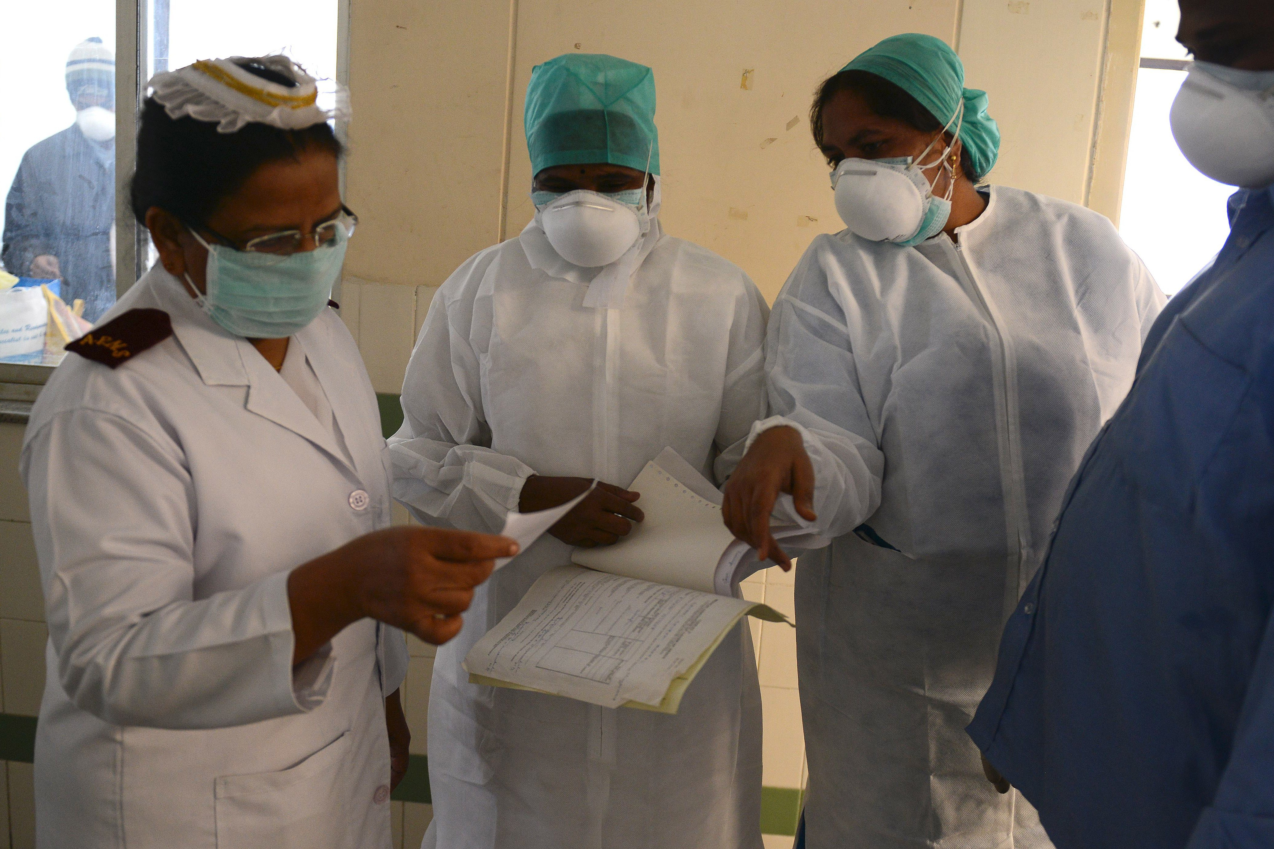 Indian health professionals inspect the case sheet of a swine flu patient at a ward at the Gandhi Hospital in Hyderabad on Jan. 21, 2015