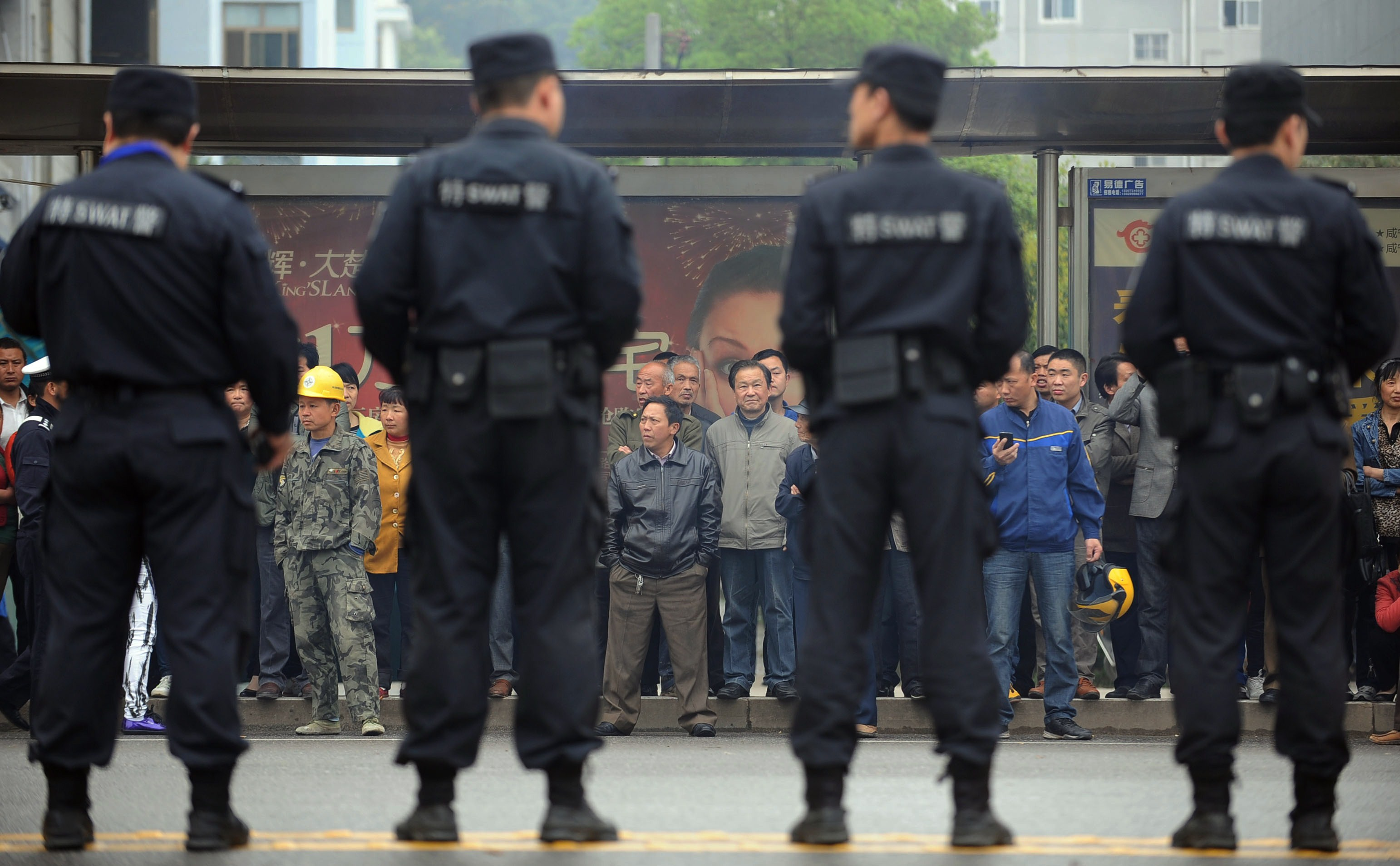 Citizens watch as police stand guard outside the Xianning Intermediate People's Court where Chinese mining tycoon Liu Han stands trial in Xianning, central China's Hubei province on March 31, 2014.