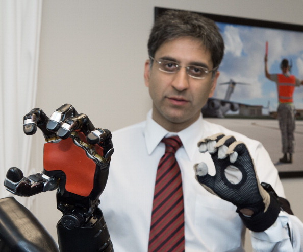 Kapil Katyal, Senior Engineer Robotics & Autonomous Systems at John Hopkins University Applied Physics Laboratory demonstrates a robotic hand and arm that responds to brain impulses seen April 22, 2014 during a briefing on DARPA sponsored  inventions at the Pentagon.  In the version seen here, the robotic hand/arm(L) mimics his real hand(R) that is wearing a sensor glove.     AFP Photo/Paul J. Richards        (Photo credit should read PAUL J. RICHARDS/AFP/Getty Images)