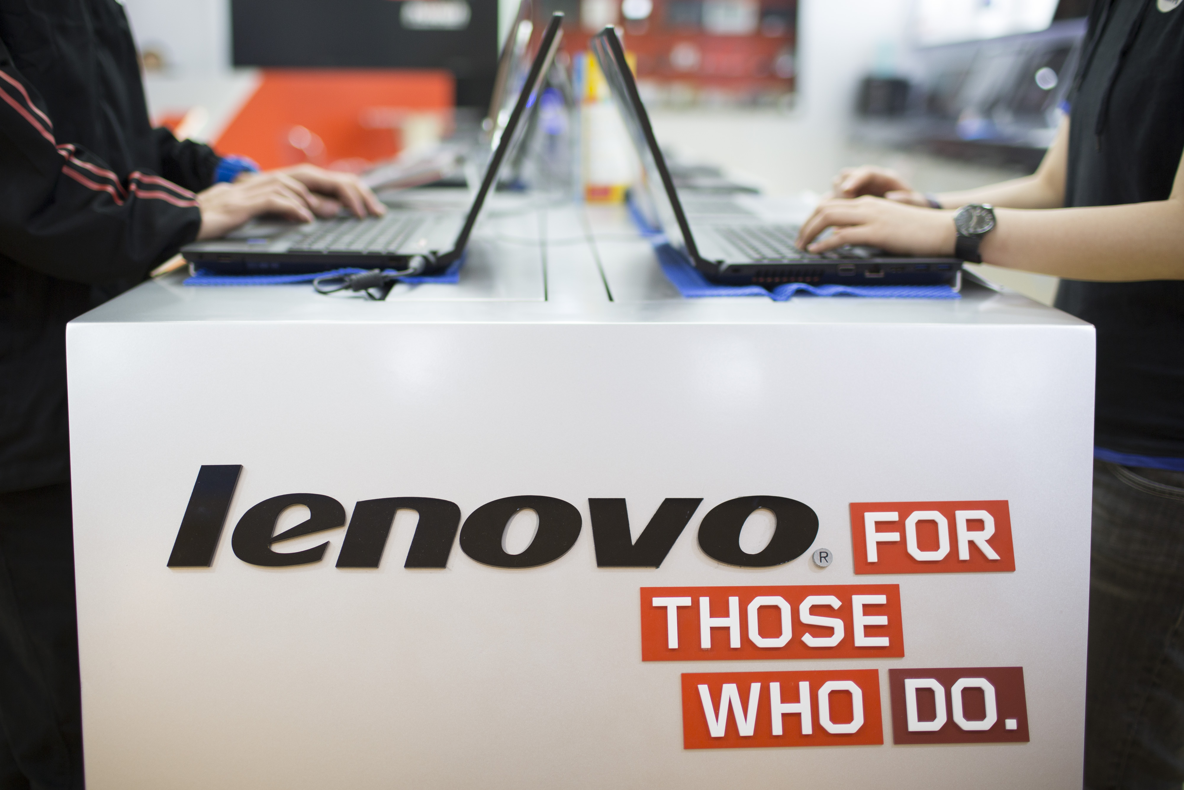 Lenovo Group Ltd. signage is displayed near laptops in an arranged photograph at a Lenovo store in the Yuen Long district of Hong Kong on May 23, 2014.