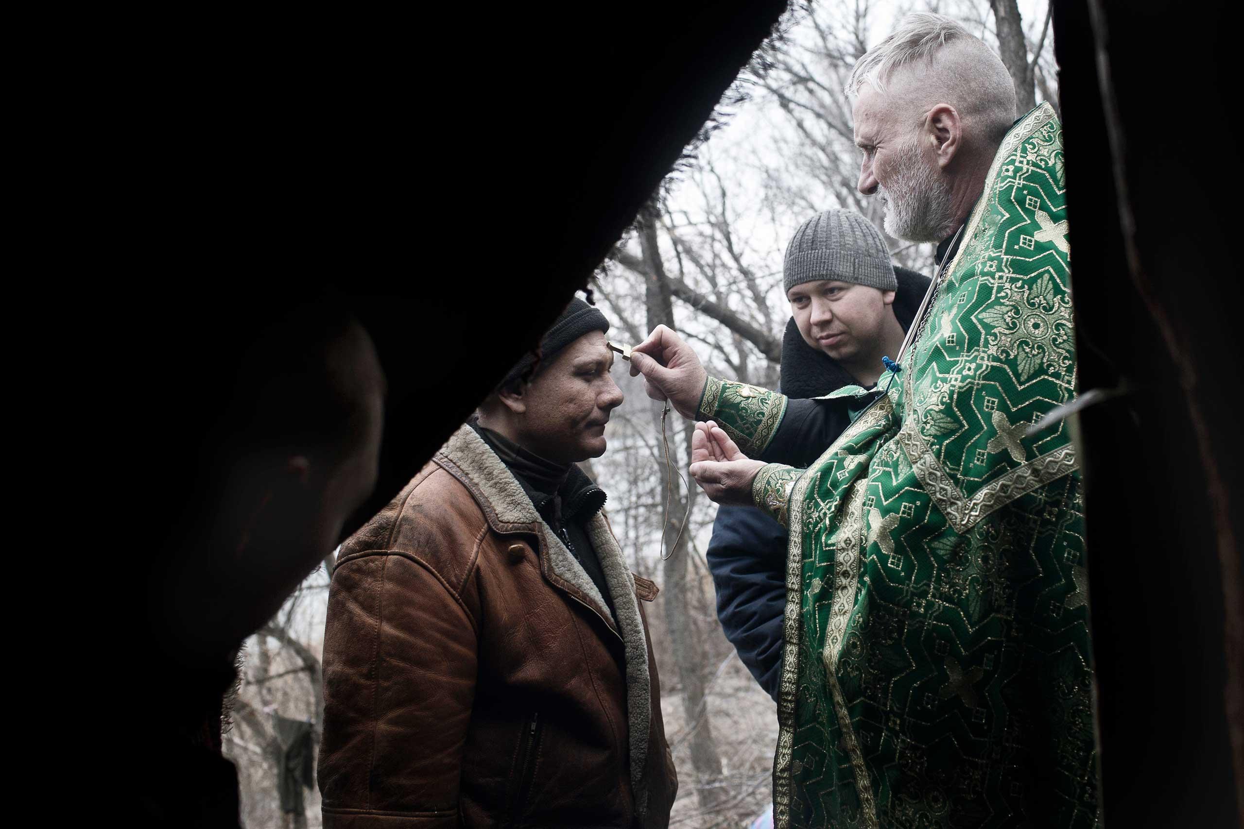 A Ukrainian Orthodox priest ministers to a volunteer member of the Aidar Battalion, a volunteer group fighting against Russian separatists in Shastya in the restive region of Luhansk, eastern Ukraine, Feb. 8, 2015.