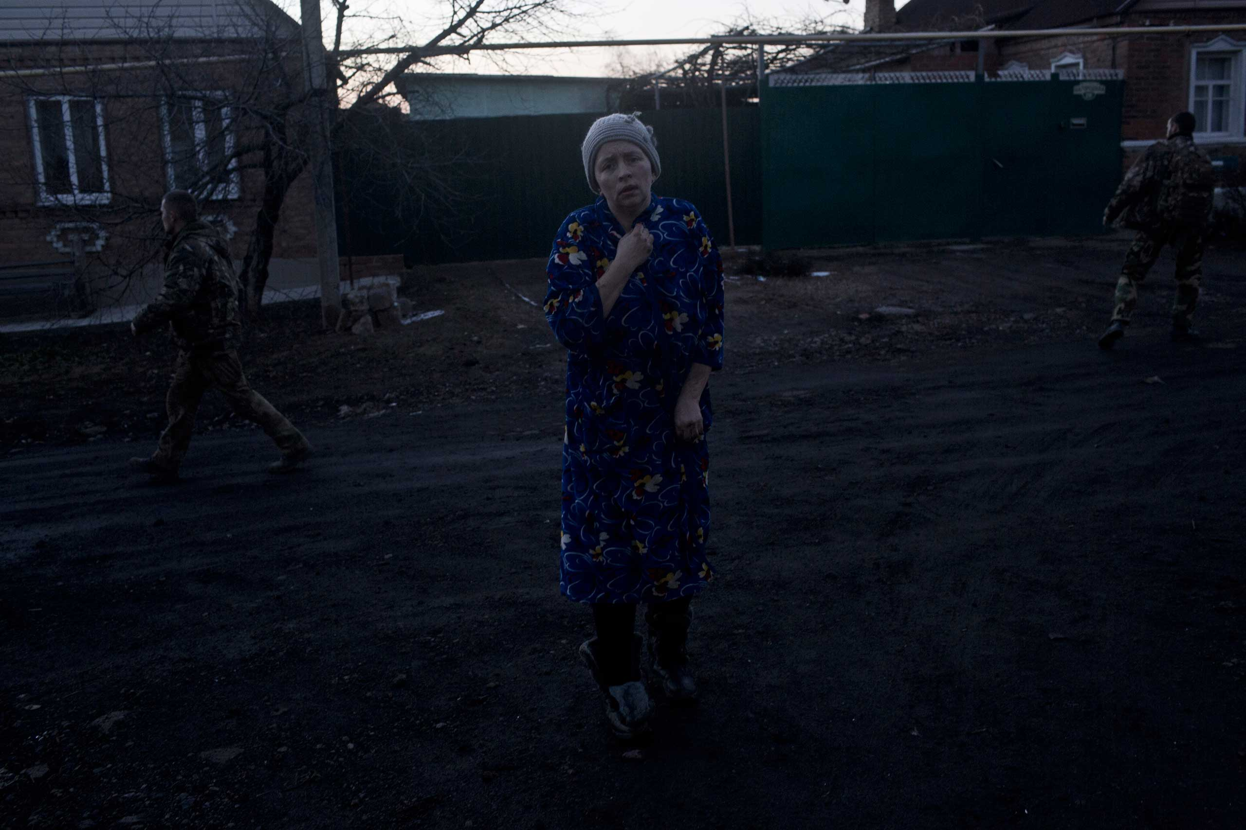 A resident walks in shock on the streets of Artemivsk after rocket fire left two dead, Ukraine, Feb. 13, 2015.