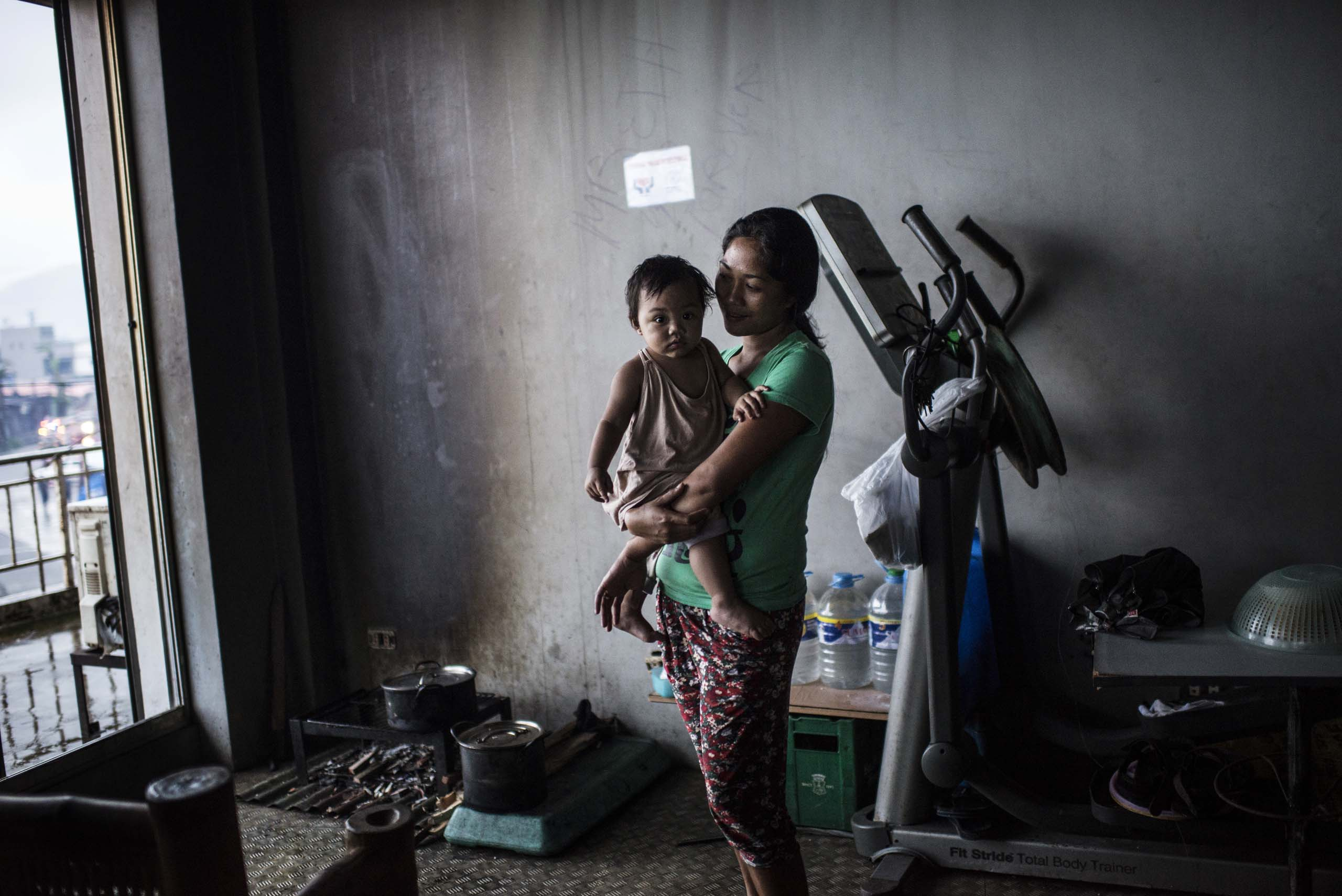 Jan.13, 2014: Displaced Philippine mother and child living inside the former gym in the stadium in Tacloban.