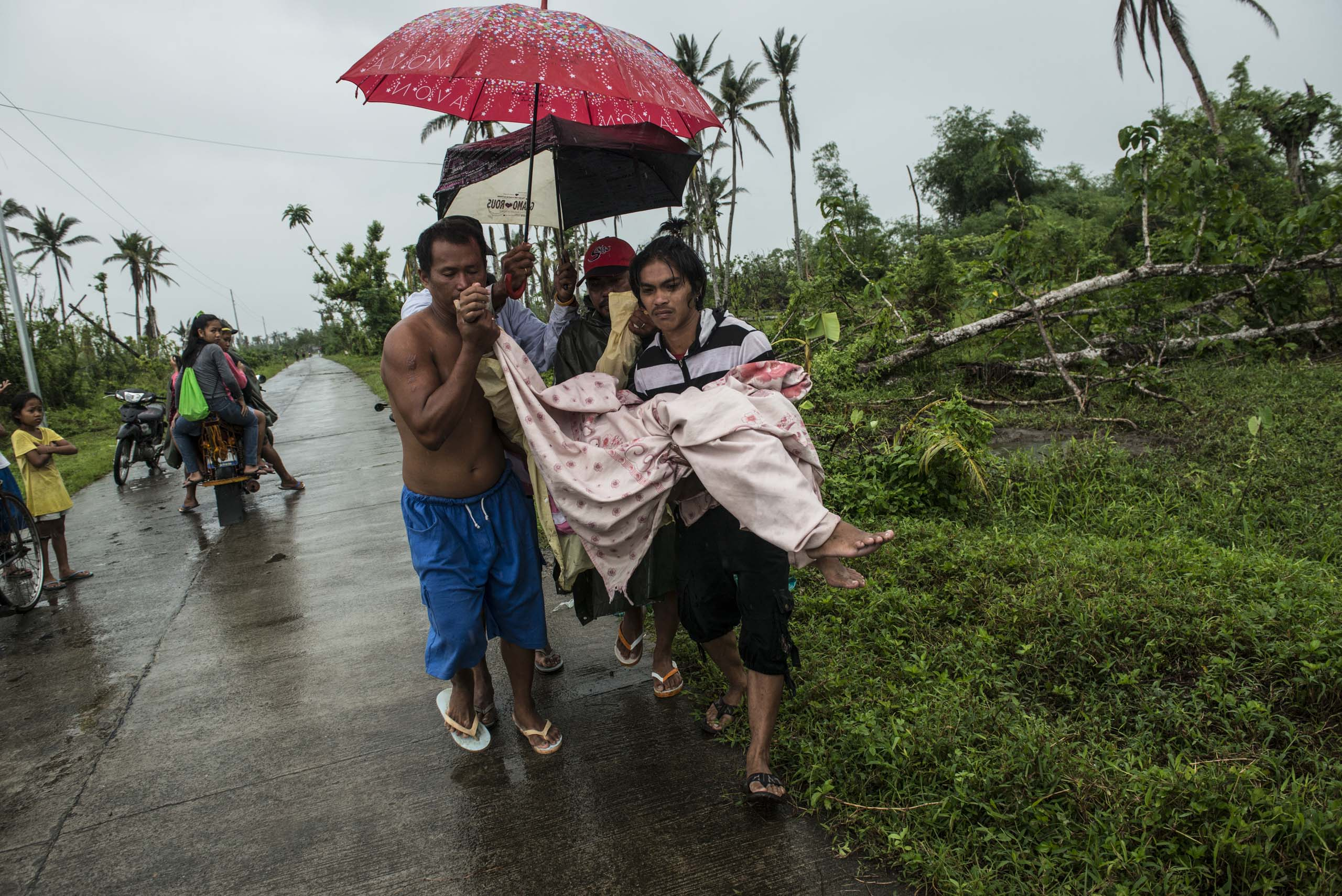 Jan.11, 2014: After the baby is born, Bacate and passersby help carry Analyn Pesado and the baby to a pickup truck on the road outside of Tacloban.