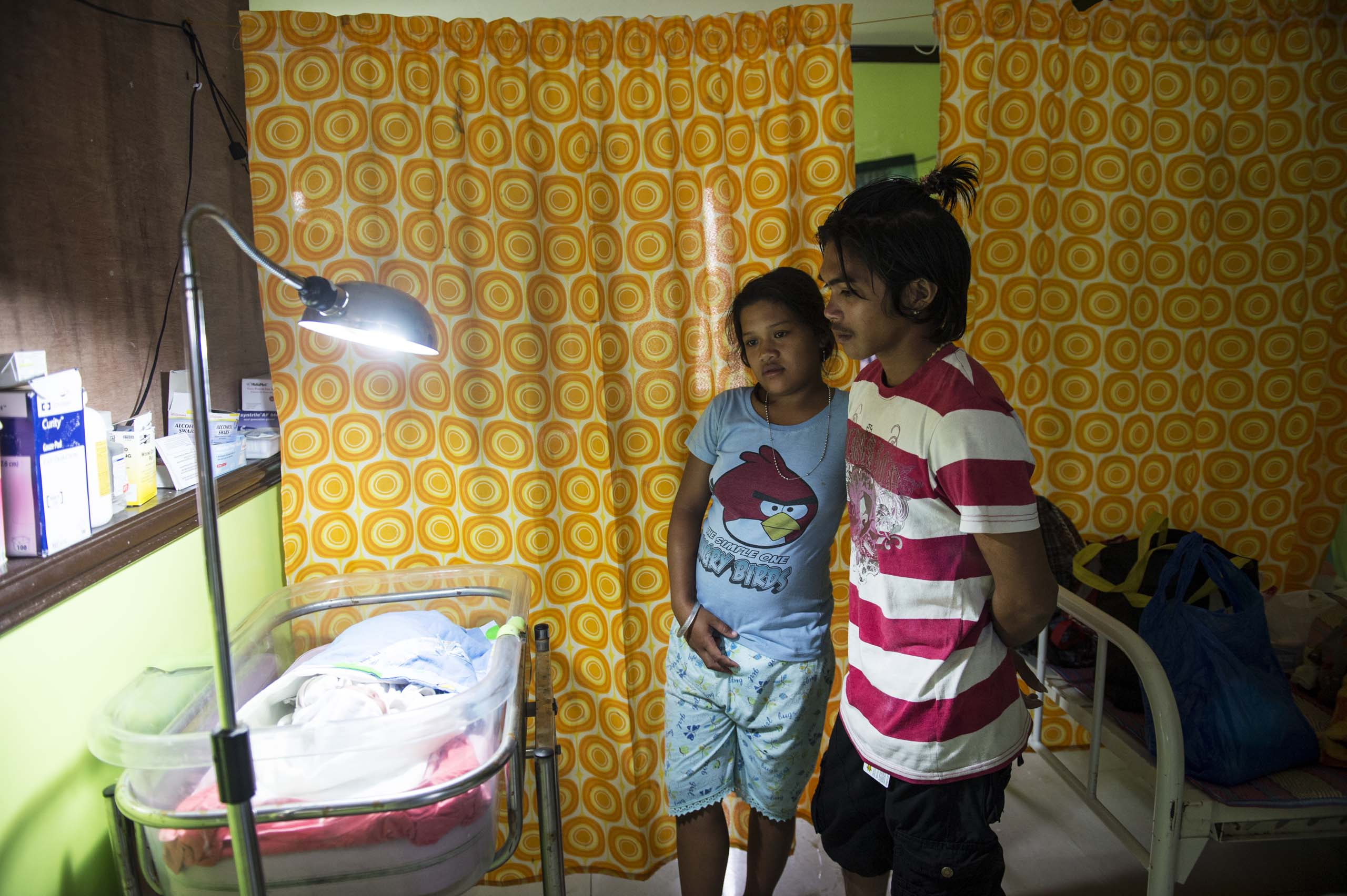 Jan.11, 2014: Analyn Pesado and Ryan Bacate watch over their new born son at the clinic in Tolosa, in the Philippines.