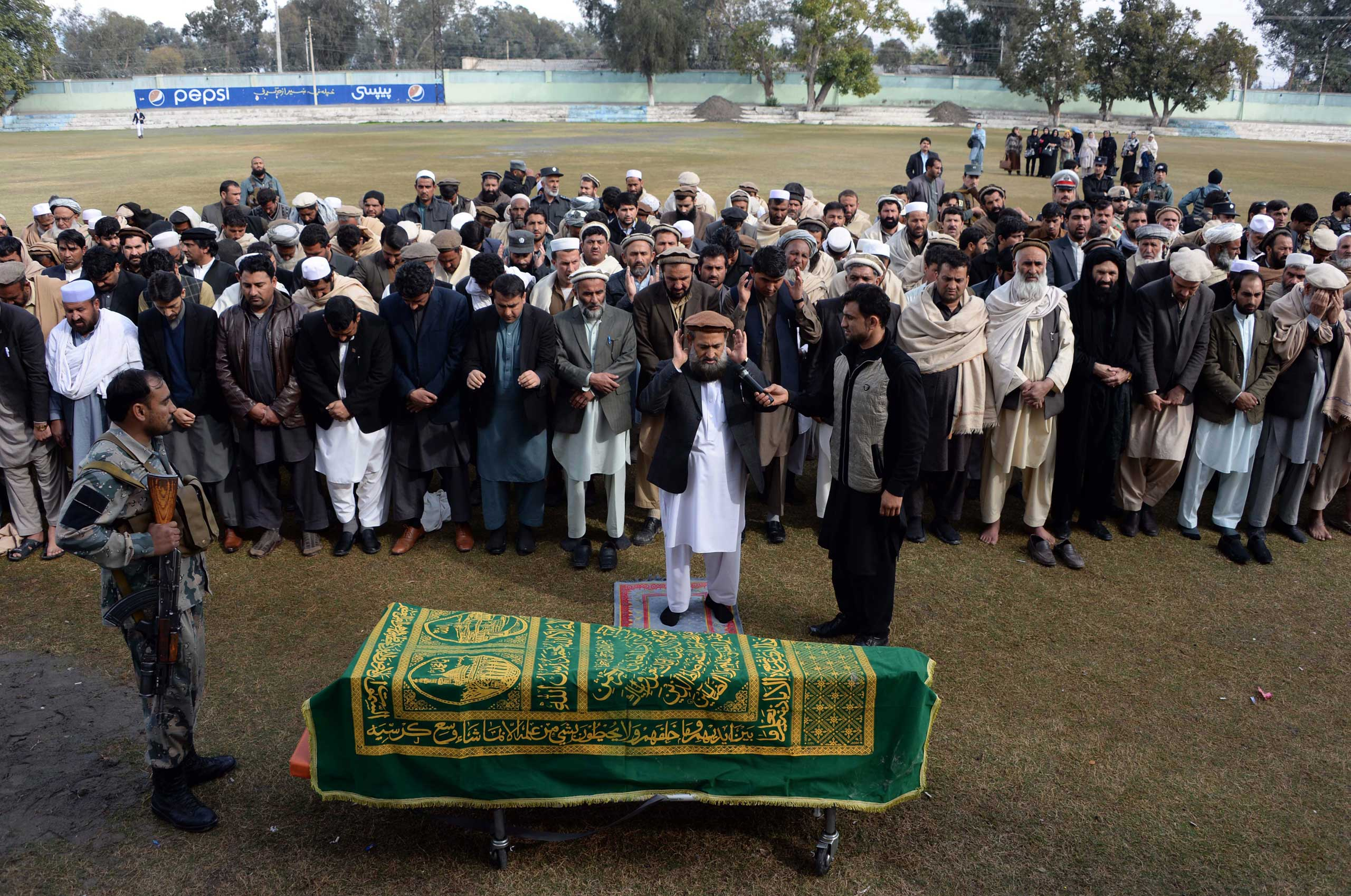 Afghan officials and mourners perform funeral prayers over the coffin of Angiza Shinwari, a provincial member, in Jalalabad on Feb. 16, 2015.