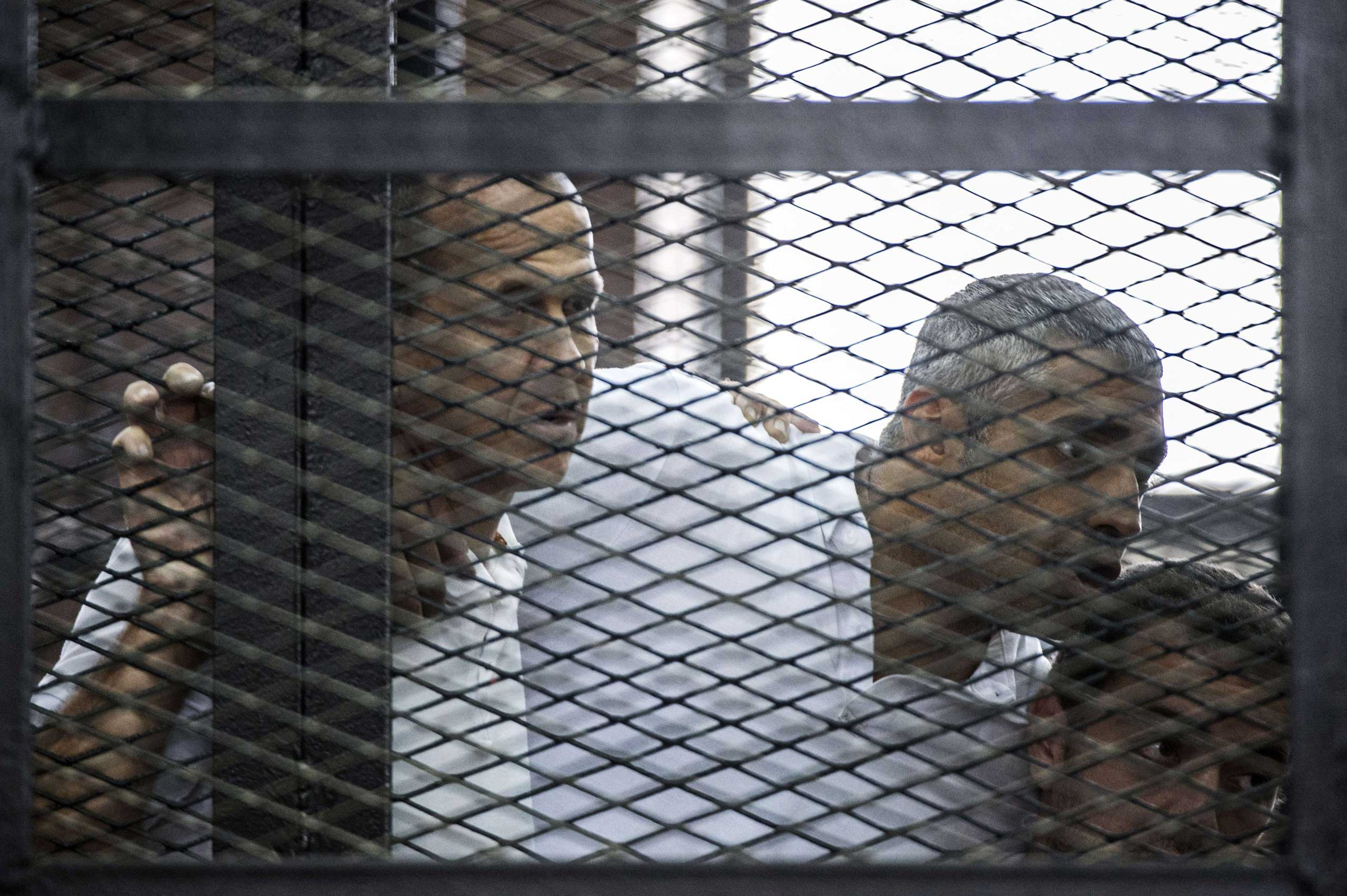Al-Jazeera news channel's Australian journalist Peter Greste (L) and his colleagues, Egyptian-Canadian Mohamed Fadel Fahmy (C) and Egyptian Baher Mohamed, listen to the verdict inside the defendants cage during their trial at Tora prison in Cairo on June 23, 2014.