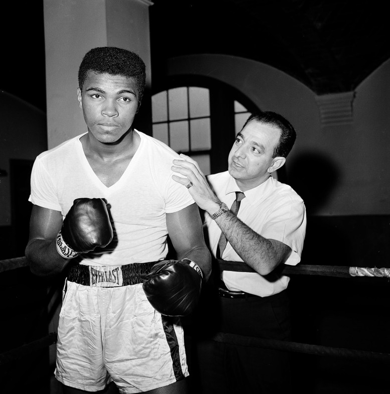 """Ali with his trainer Angelo Dundee in New York City, 1962                                                              Angelo Dundee: """"I first met Ali in 1958. I was in Louisville, Ky. I get a call from the lobby. I start talking to this kid who says his name is Cassius Clay and that he is going to win the Olympics. He was 16. I am wondering, Who is this nutcase? But we met. He was a student of boxing. He asked about what my fighters ate, when they stopped road work before a fight. He was hungry to learn about boxing. A few hours later we stopped talking. I didn't really train amateurs. He asked about training with me. Other people were offering him money and cars. I said, 'All I can offer you is me.' He came down to Miami. He kept asking me to spar with my fighters. One day, I have him spar with one of my champions. My fighter didn't look good against Ali, and when he came to the corner, I told him, 'You're going stale!'  He said, 'No, I just couldn't hit the guy.'  I had 16 fighters in my gym, and he became one of the guys. Someone started calling him Big Mouth. He liked to talk. And that was important. I made him accessible to the reporters. I had more fun with Ali than anyone in my life.                                                               No, I don't consider him a son. A trainer can't ever be his fighter's father. Never consider a fighter a son — you can't help him. You can't do the right thing by him.You can't take care of your own child if they have a cut, or your hand starts shaking. He is my friend. Ali has so many qualities as a human being. Back then, I had him to my house three Christmases in a row. He entertained everyone. He was the first to arrive and the last to leave. One of the greatest things that happened to the human race, having Ali around."""" Angelo Dundee, 90, was Ali's trainer and was in his corner for more than 20 years, from 1960 to 1981."""