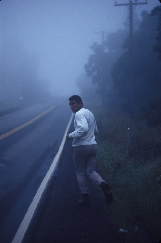 Ali training in Deer Lake, Pa., 1974                               Ken Regan:  I was on assignment for TIME magazine to shoot Muhammad Ali at his training camp in Deer Lake, Pa. I wanted to photograph Muhammad running early in the morning because there was always a lot of fog on the river where he used to run; I thought it would make a interesting visual. The problem was, Muhammad didn't like to get up in the morning and train that early; he only liked to train in the afternoon. After numerous conversations with Muhammad and his manager, he reluctantly agreed to do it for me. I was following him that morning in a car with a retractable roof. We were out about 10 minutes, and Muhammad turned around toward me and said, 'Are we done yet?' That is the photograph that I ended up using. He immediately went back to his camp and went to bed.  Ken Regan is a photographer and filmmaker.