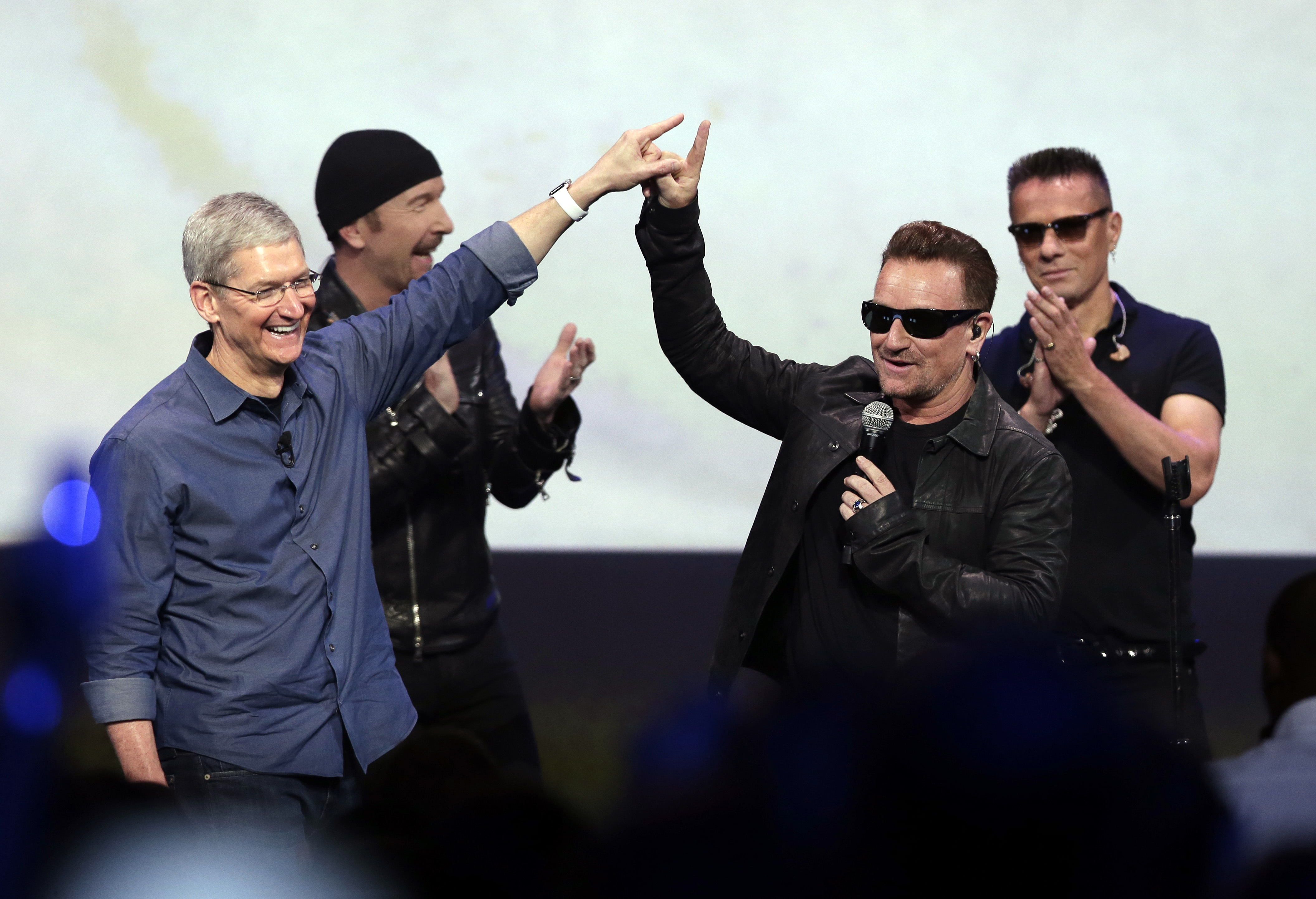 In this Sept. 9, 2014 file photo, Apple CEO Tim Cook (L) greets Bono from the band U2 after they preformed at the end of the Apple event in Cupertino, Calif.