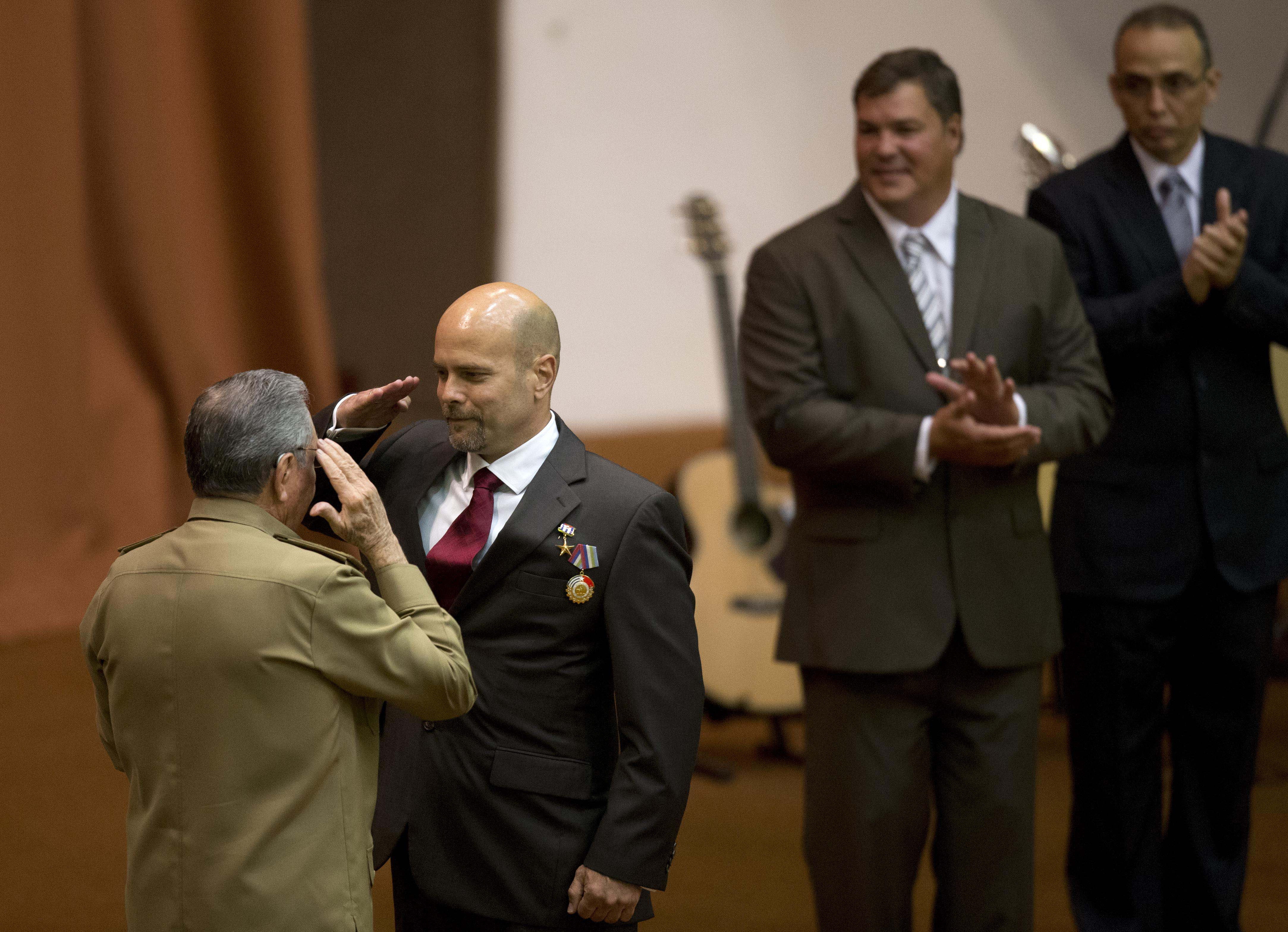 Cuba's President Raul Castro and Gerardo Hernandez salute, as fellow agents Ramon Labanino, background, second from right, and Antonio Guerrero applaud during a medal ceremony, in Havana, Cuba, Tuesday, Feb. 24, 2015