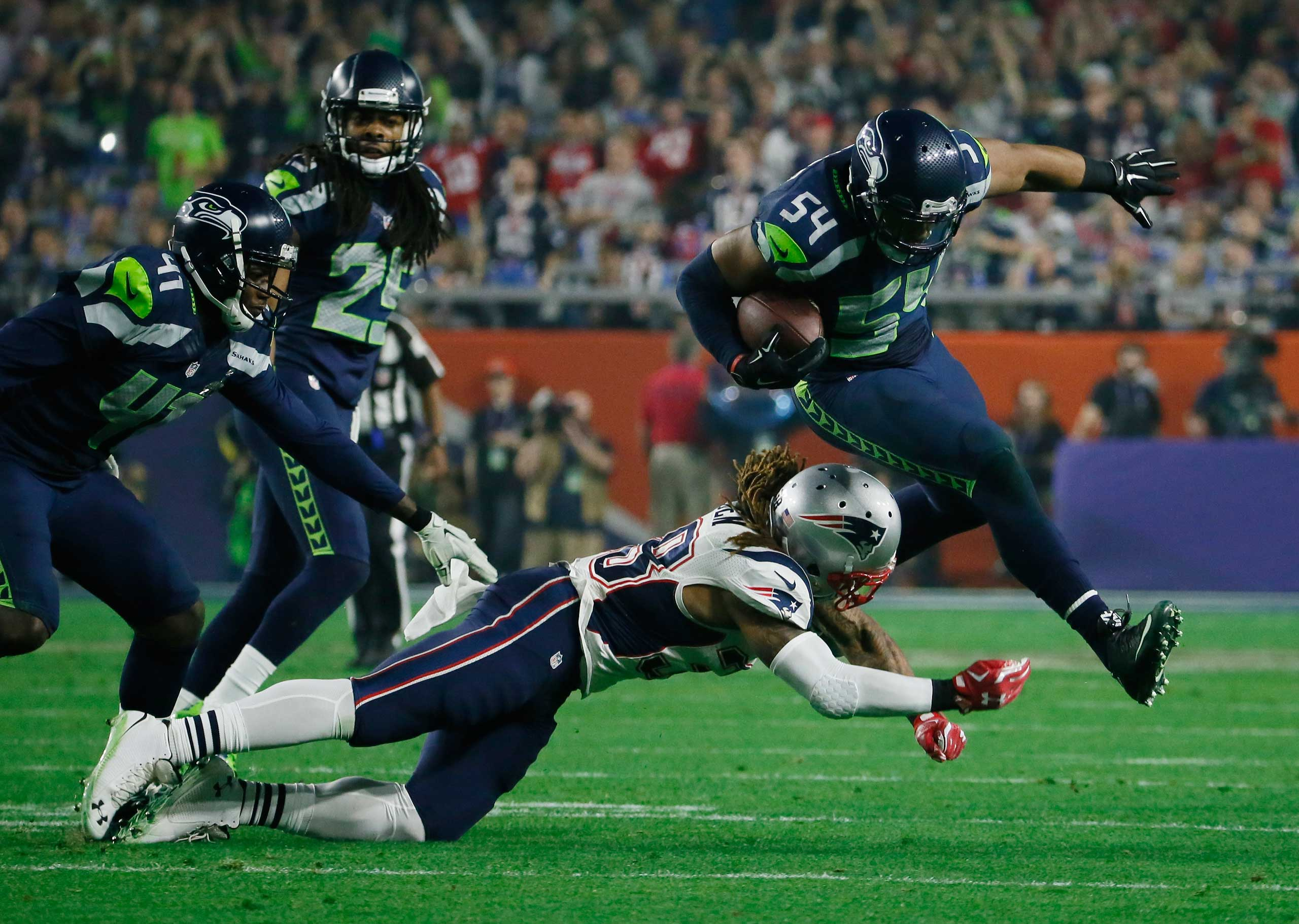 Seattle Seahawks middle linebacker Bobby Wagner (54) gets past New England Patriots running back Brandon Bolden (38) after intercepting a pass during the second half of NFL Super Bowl XLIX football game Sunday, Feb. 1, 2015, in Glendale, Ariz.