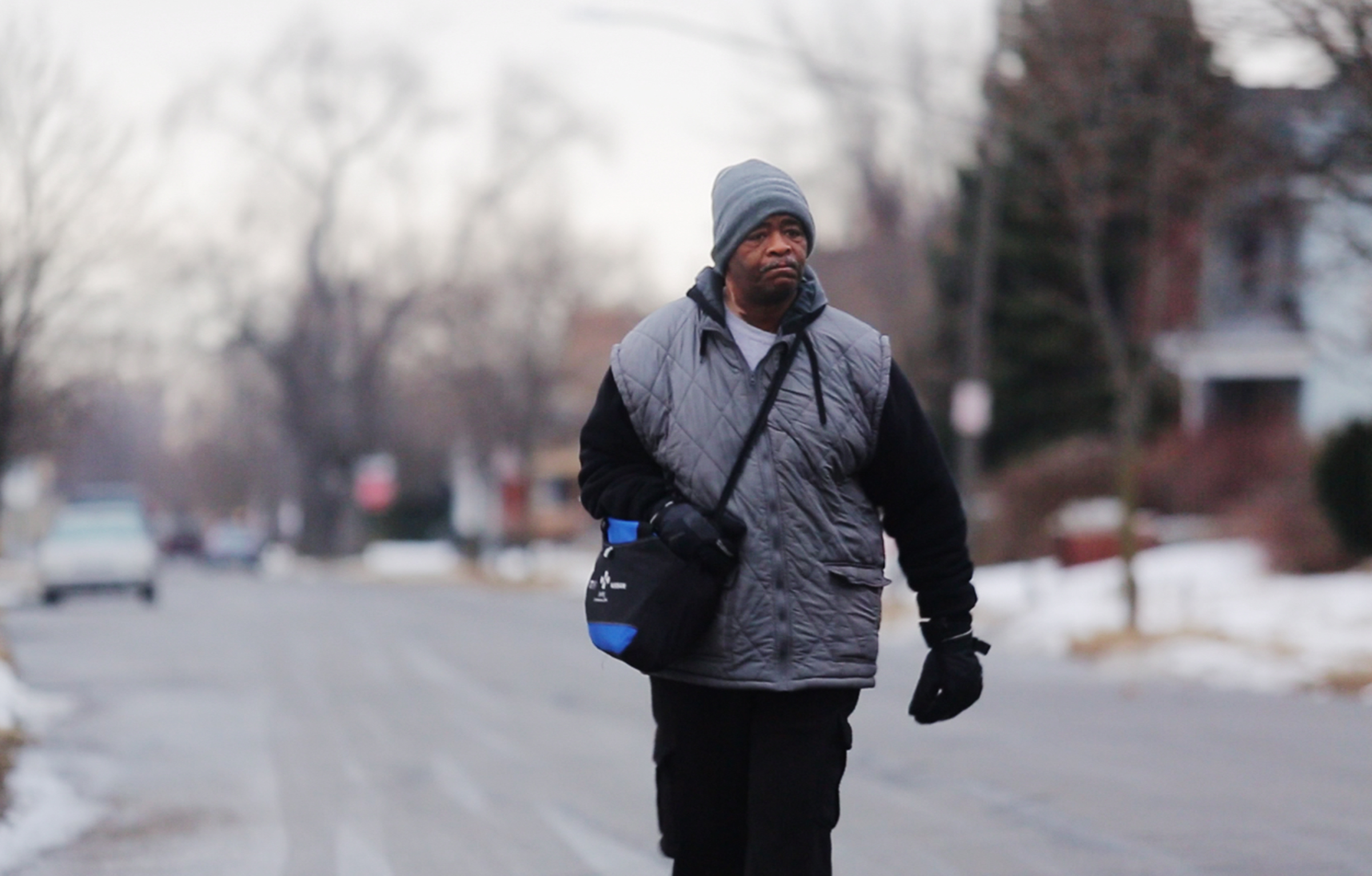 In this Jan. 29, 2015, photo, James Robertson, 56, of Detroit, walks toward Woodward Aveune in Detroit to catch his morning bus to Somerset Collection in Troy before walking to his job at Schain Mold Engineering in Rochester Hills. Getting to and from his factory job 23 miles away in Rochester Hills, he'll take a bus partway there and partway home and walk 21 miles according to the Detroit Free Press