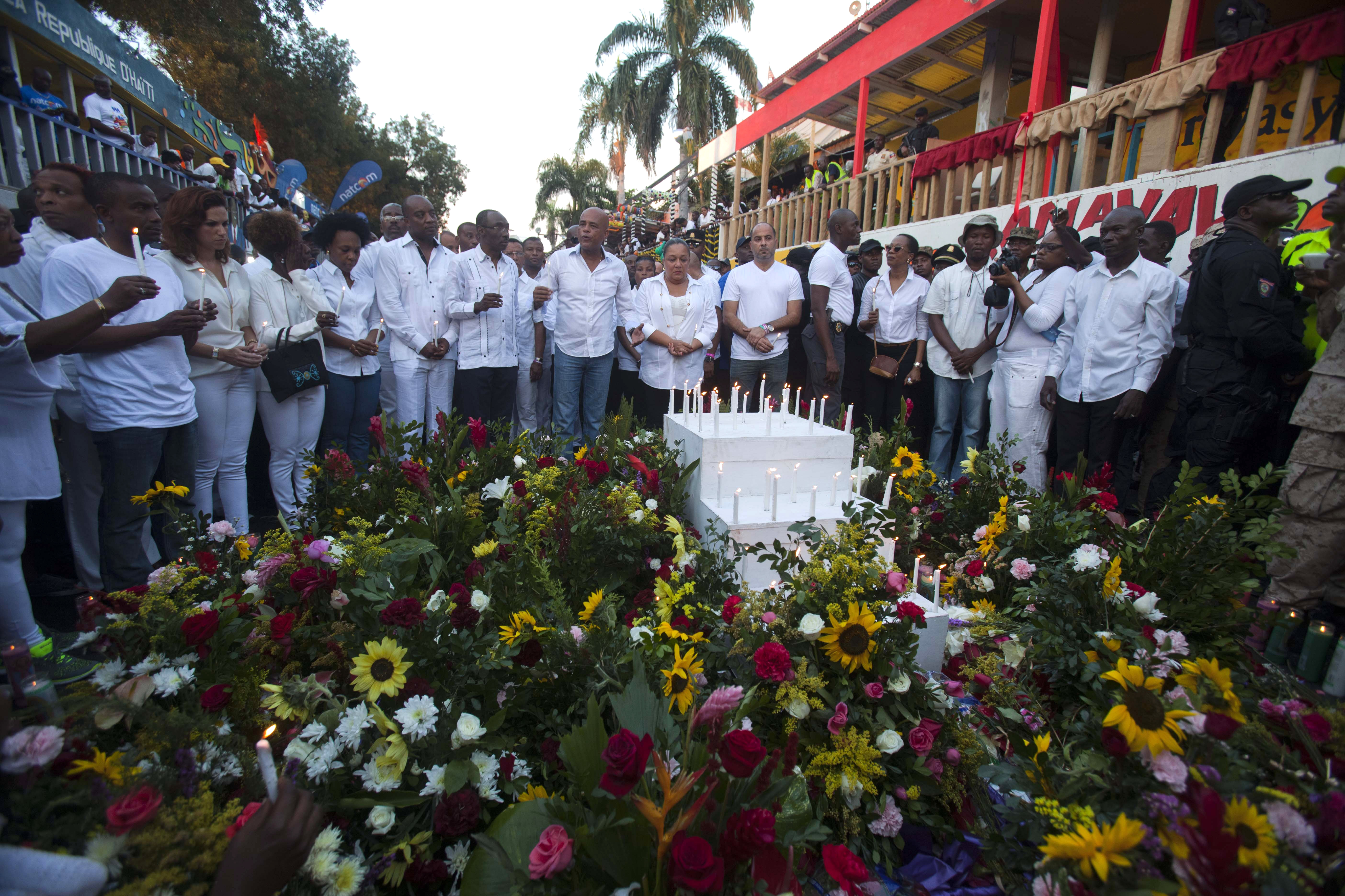 Haiti's President Michel Martelly, center left, and first lady Sophia Martelly, right center, stand at a memorial in Port-au-Prince, Haiti, Feb. 17, 2015