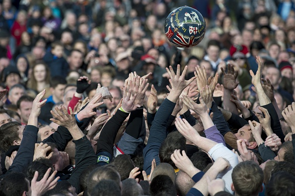 Opposing teams of the Up'ards and the Down'ards reach for the ball as they compete in the annual Royal Shrovetide Football Match in Ashbourne, Derbyshire, England on February 17, 2015.